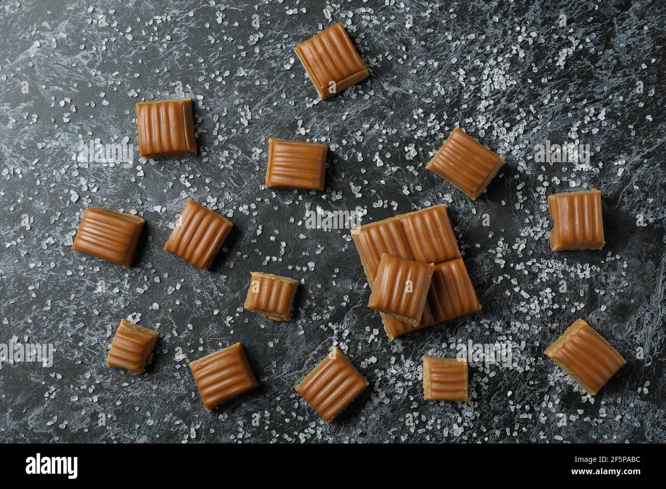 Trozos de caramelo salados sobre fondo negro ahumado Foto de stock