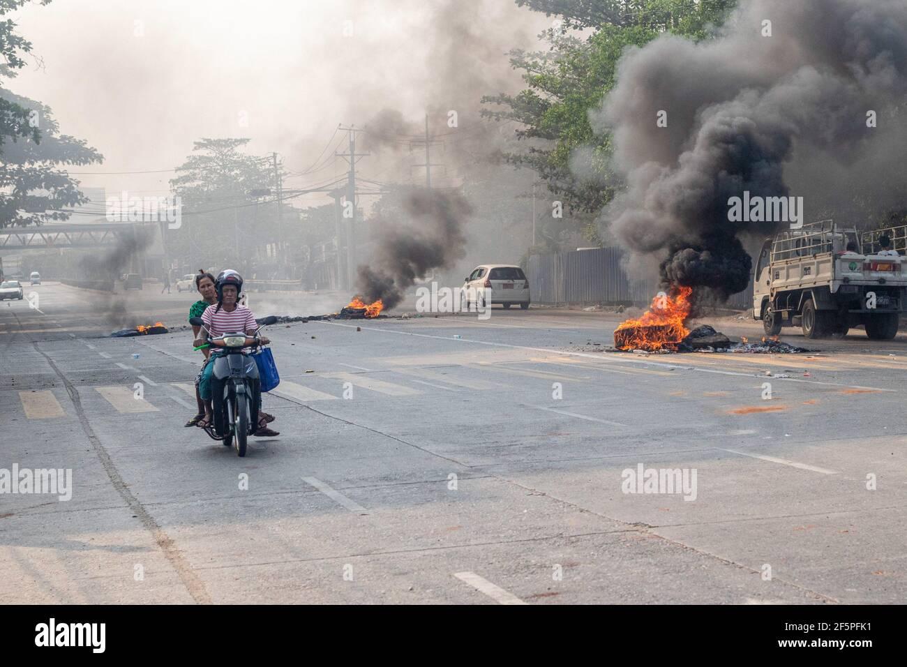Durante una protesta contra el golpe militar, un motociclista pasa por neumáticos quemados en la calle.la policía y los soldados militares de Myanmar (tatmadow) atacaron a los manifestantes con balas de goma, municiones vivas, gases lacrimógenos y bombas de aturdimiento en respuesta a los manifestantes contra el golpe militar el sábado, matando a más de 90 personas e hirieron a muchas otras. Al menos 300 personas han sido asesinadas en Myanmar desde el golpe de Estado del 1 de febrero, dijo un funcionario de derechos humanos de la ONU. El ejército de Myanmar detuvo a la Consejera de Estado de Myanmar, Aung San Suu Kyi, el 01 de febrero de 2021, y declaró el estado de emergencia mientras se apoderaba del povo Foto de stock
