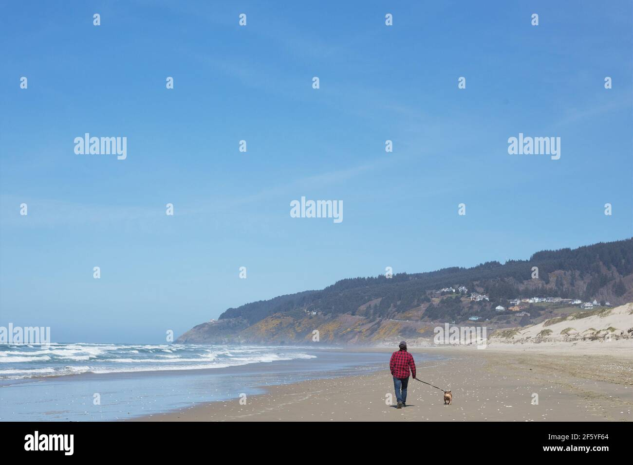 Un hombre caminando a un perro en Baker Beach en Florencia, Oregon, Estados Unidos. Foto de stock