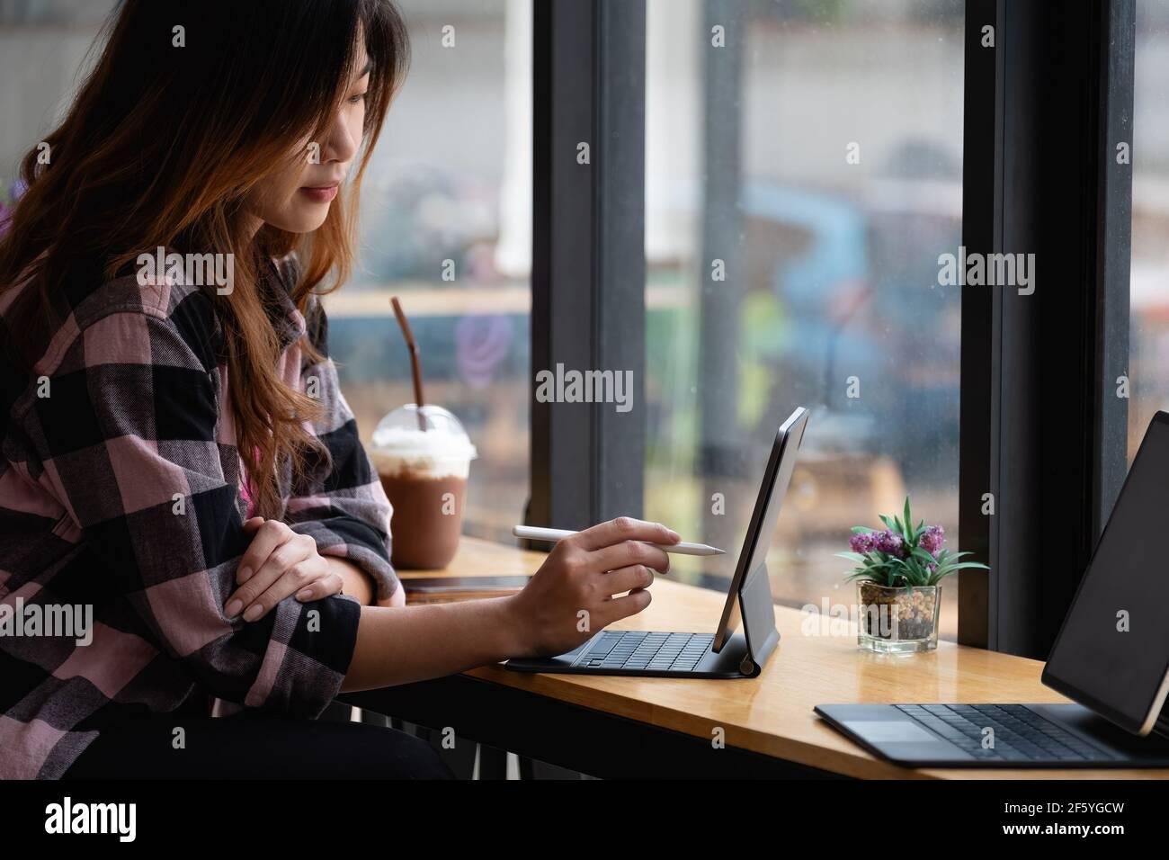 Joven diseñador creativo sosteniendo el lápiz de lápiz de dibujo en la pantalla de tableta digital en el café Foto de stock