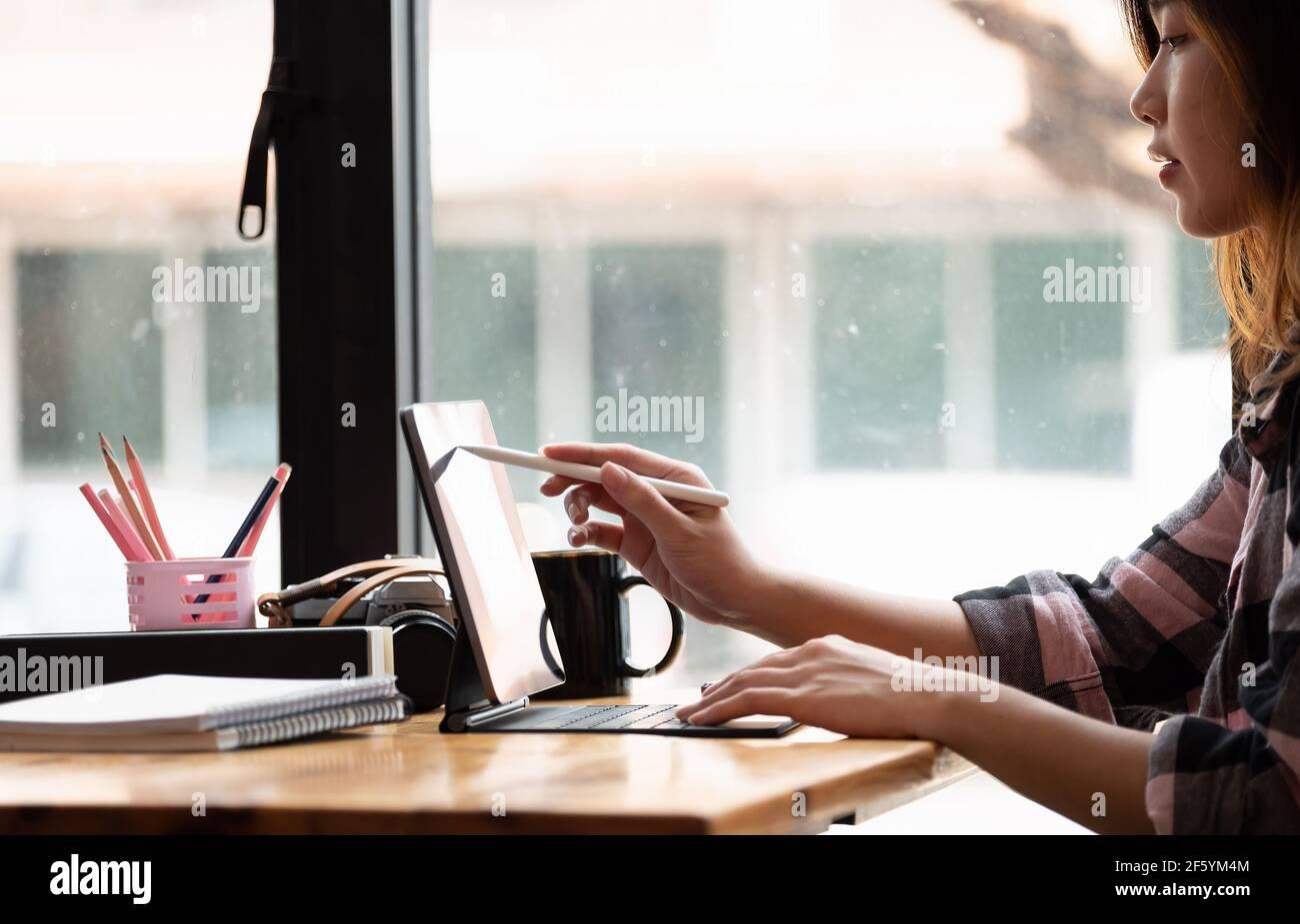 Asian Graphic Designer trabaja con un monitor interactivo, una tableta de dibujo digital y un lápiz Foto de stock