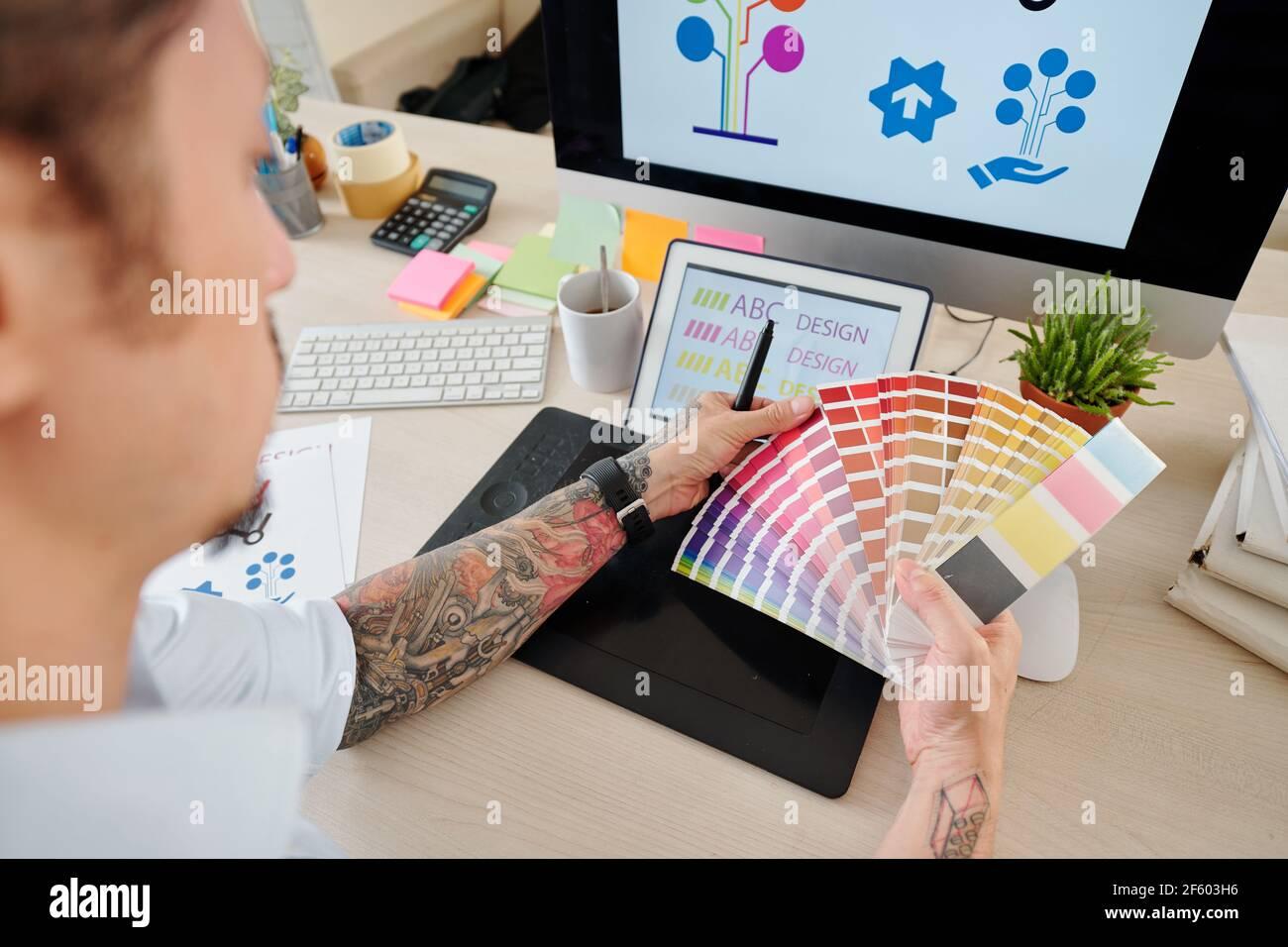 Manos de diseñador gráfico mirando la paleta y elegir el color para la empresa Foto de stock