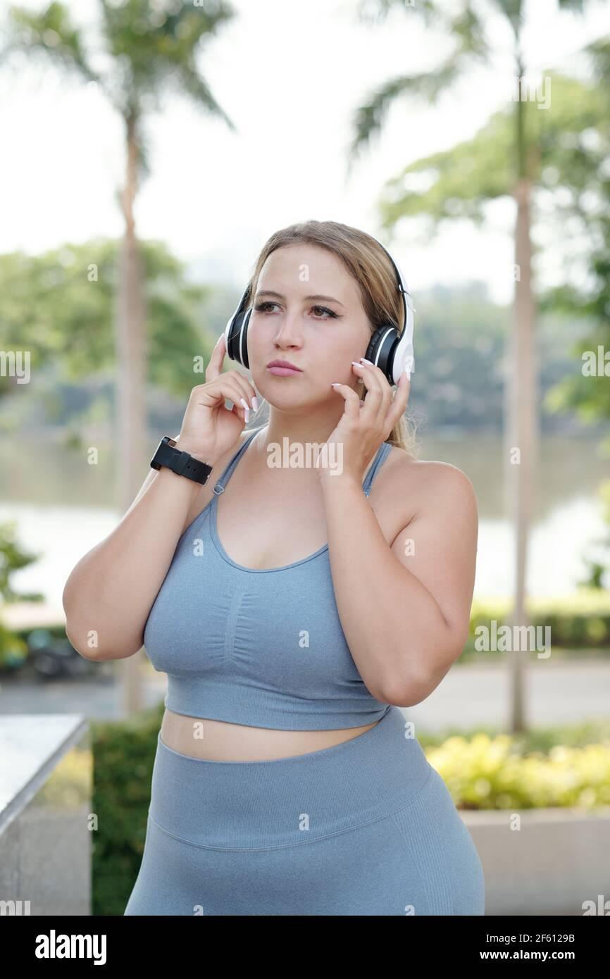 Bastante en forma más tamaño joven mujer escuchando música en auriculares después de salir al aire libre Foto de stock
