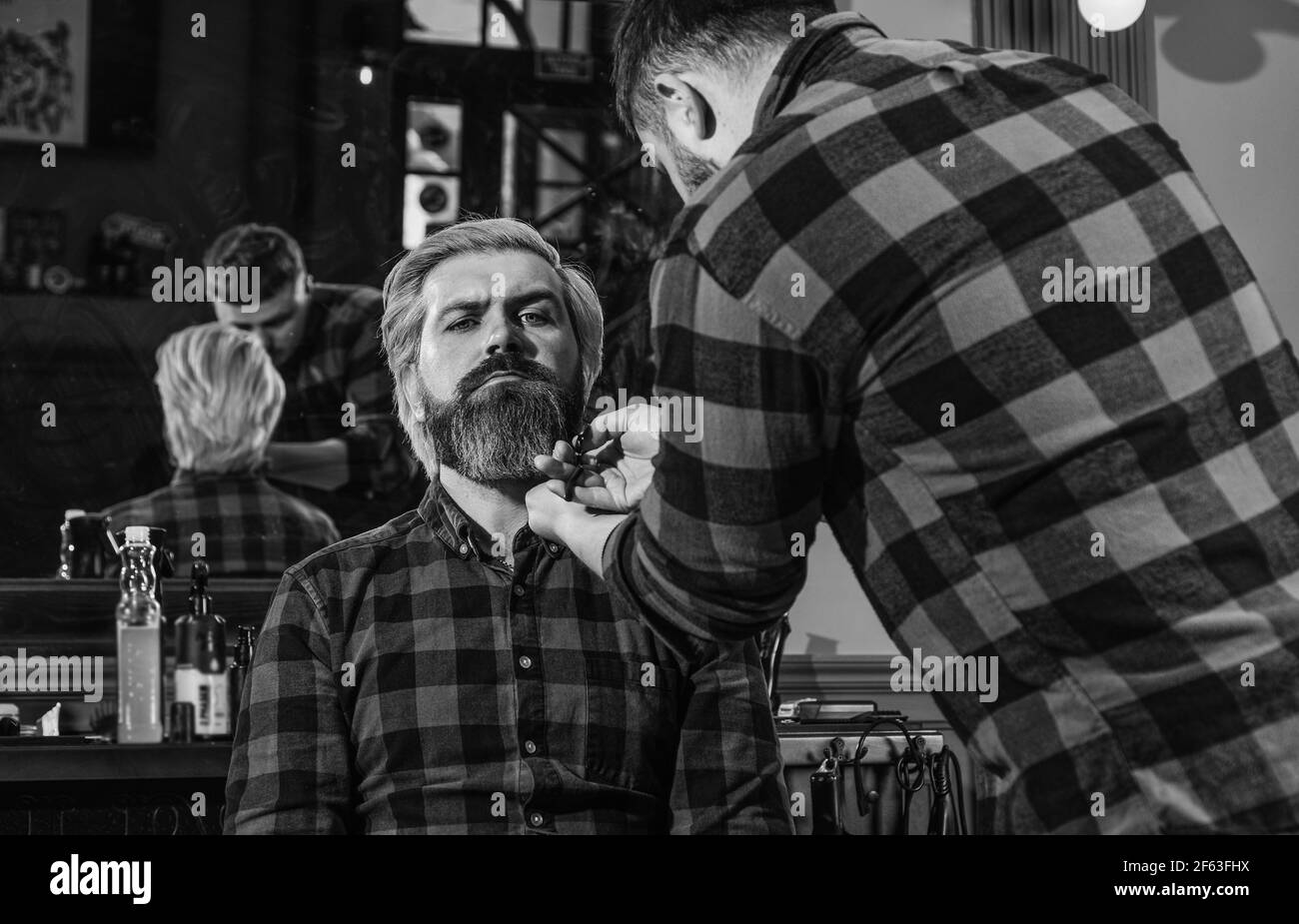 Retrato de masculinidad. Maestro barber hace el peinado y peinado con secador. Barbería. Joven hombre de cintura baja con barba cortando el pelo en un Foto de stock