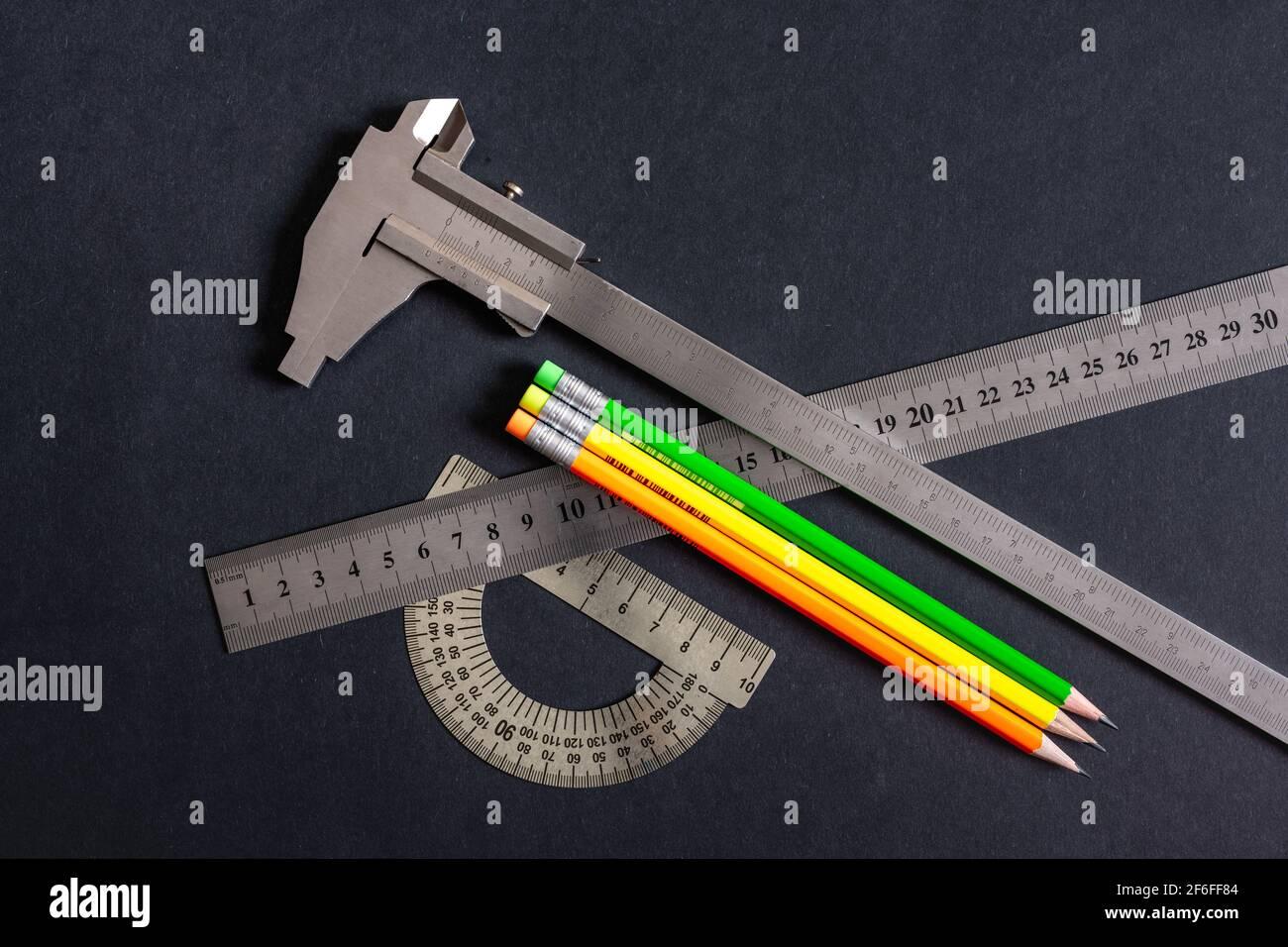 Goniómetro y regla y nonio calibre tres tipos sobre patrones de fondo gris-negro oscuro. Sketching lápices verde amarillo naranja. No color, monochr Foto de stock