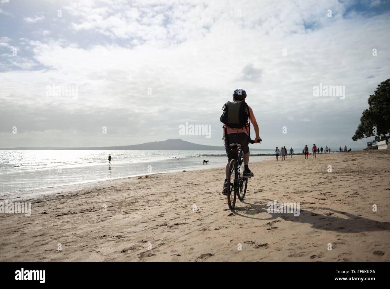 Un hombre en bicicleta en la playa de Milford con la isla Rangitoto en la distancia. Gente y perros desenfocados caminando por la playa. Foto de stock
