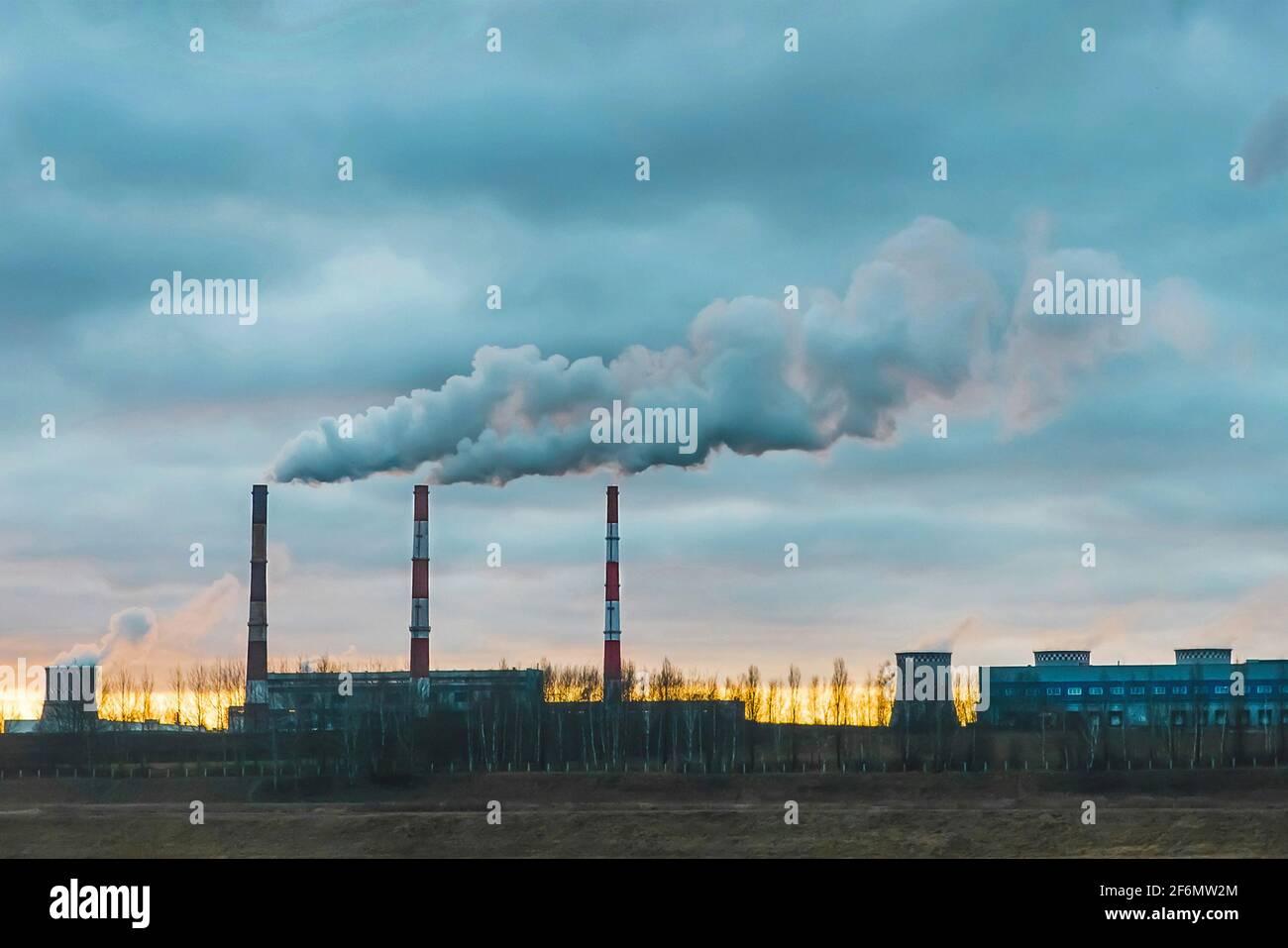 Contaminación ambiental, problema ambiental, humo de la chimenea de una planta industrial o central térmica contra un cielo azul nublado. Foto de stock