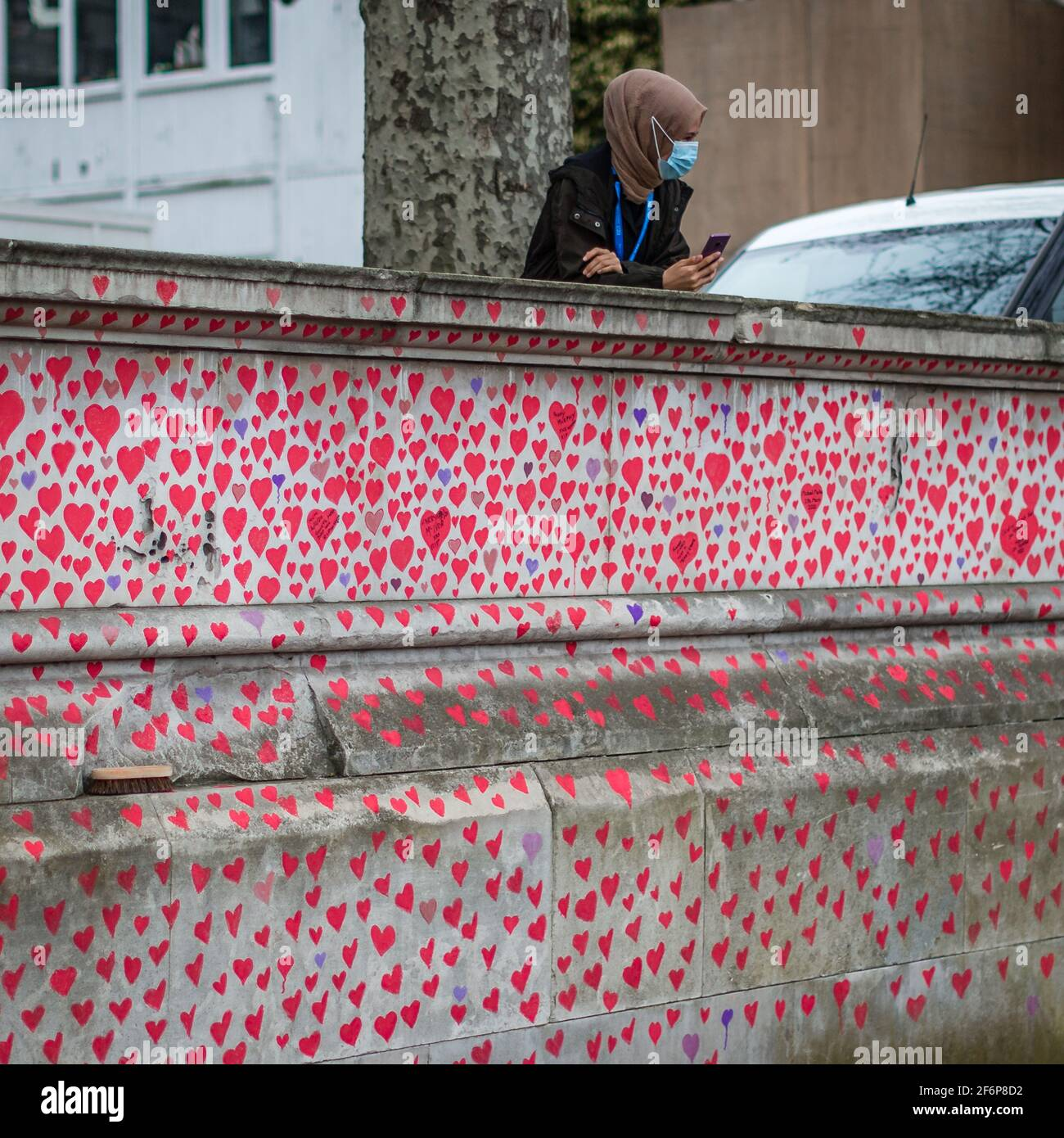Un trabajador enmascarado del NHS por encima del National Covid Memorial Wall en Londres. Foto de stock