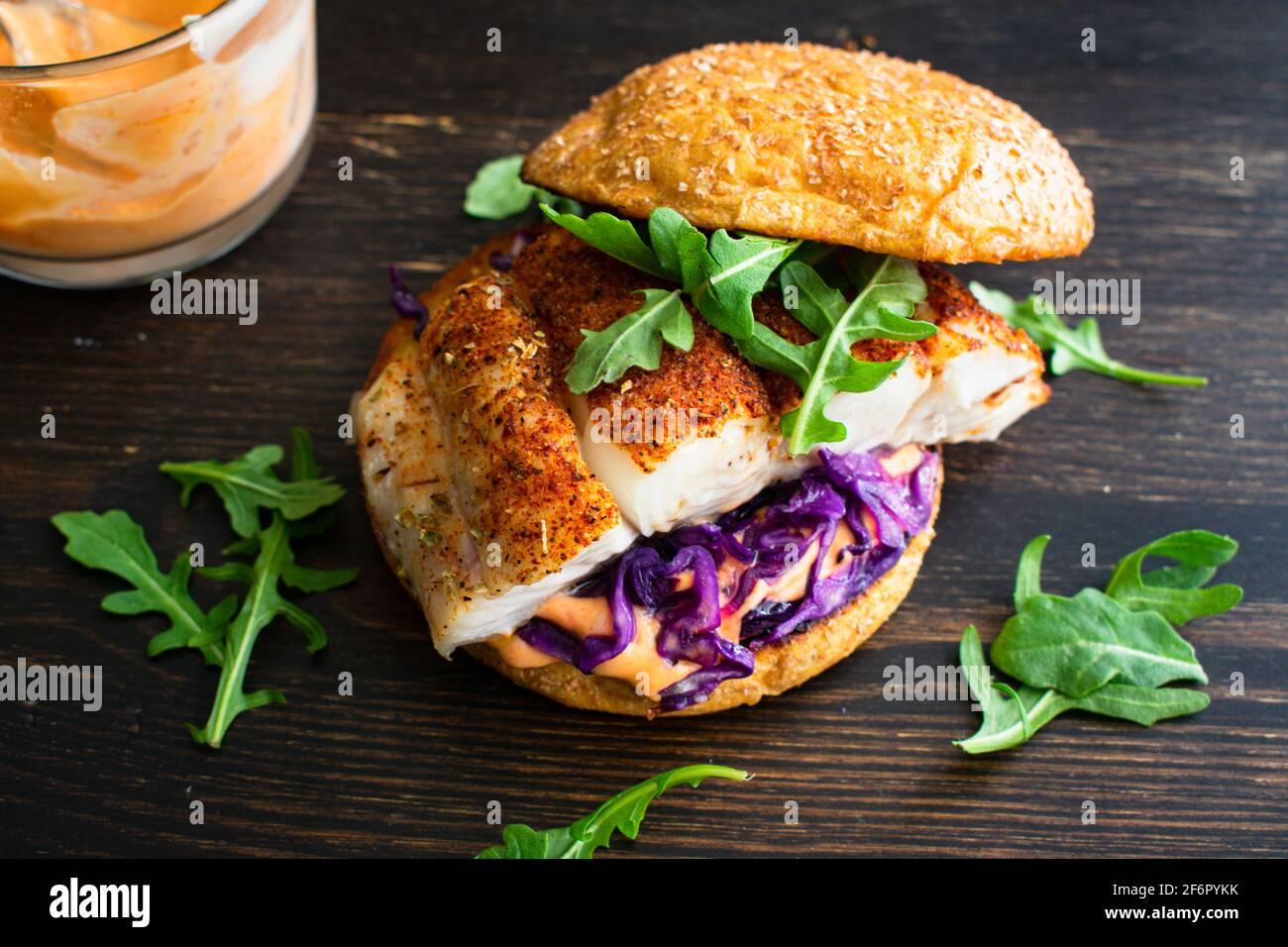 Hamburguesa de pescado ennegrecido y Sriracha Mayo: Un sandwich de pescado de halibut con col roja y arúgula en un bollo entero de brioche de trigo Foto de stock