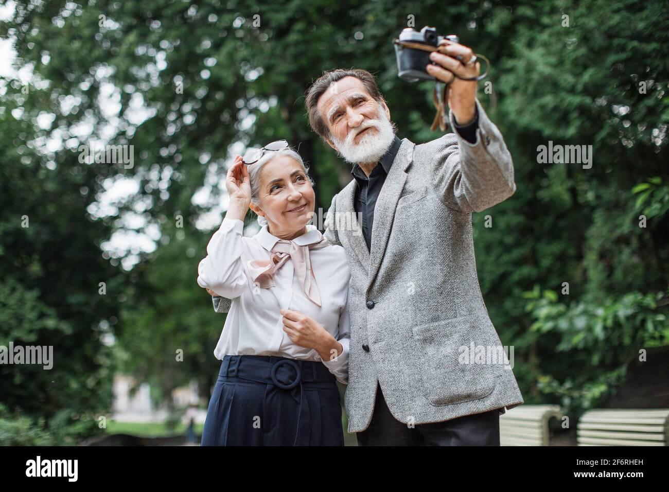 Hermosa familia mayor con ropa elegante que toma autorretrato en cámara retro. Feliz esposa y marido de pie en Green Park y disfrutar del tiempo soleado. Foto de stock