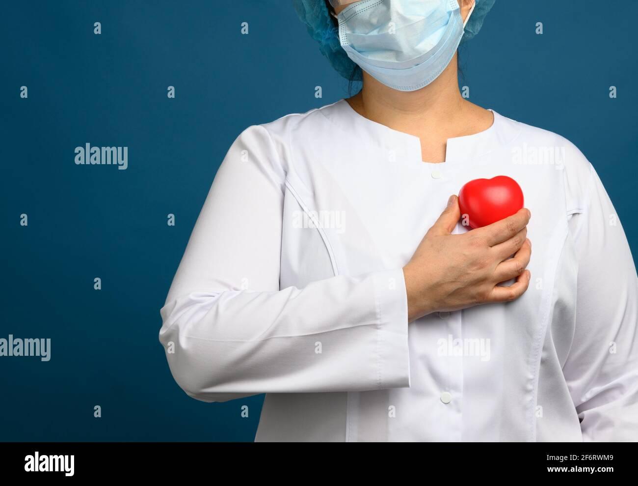 médico femenino en un abrigo blanco, una máscara se levanta y sostiene un corazón rojo sobre un fondo azul, el concepto de donación y amabilidad. Foto de stock
