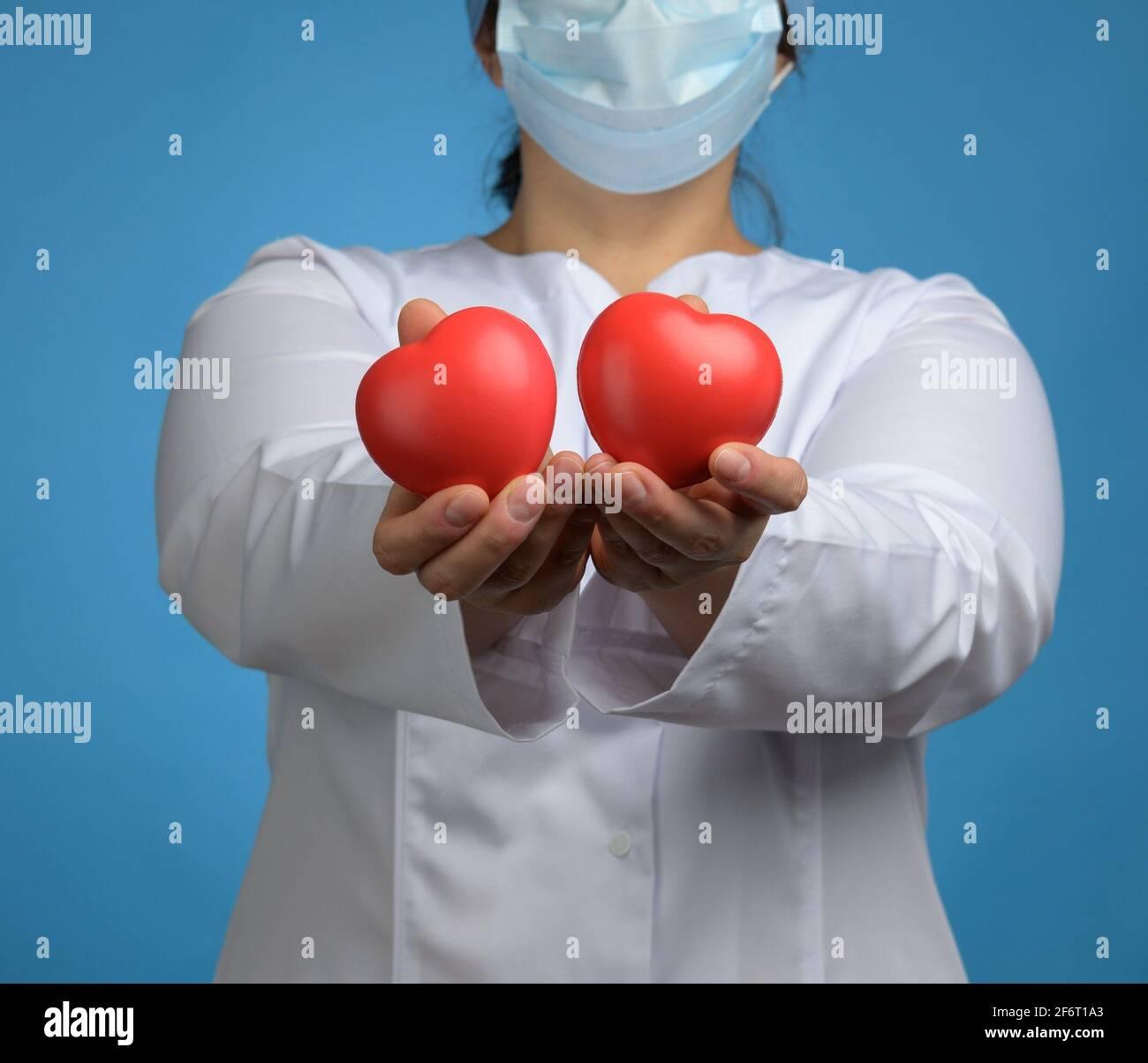 médica en un abrigo blanco, una máscara se levanta y sostiene un corazón rojo sobre un fondo azul, el concepto de donación y amabilidad. Foto de stock