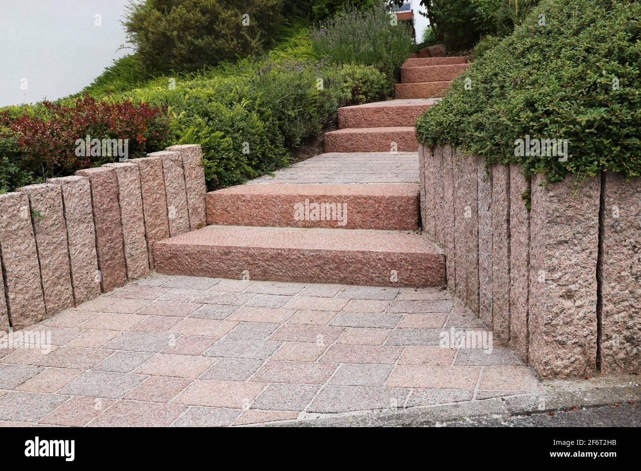 Jardín frontal ordenado y ordenado con escalones de bloques sólidos, grava decorativa y plantación. Foto de stock