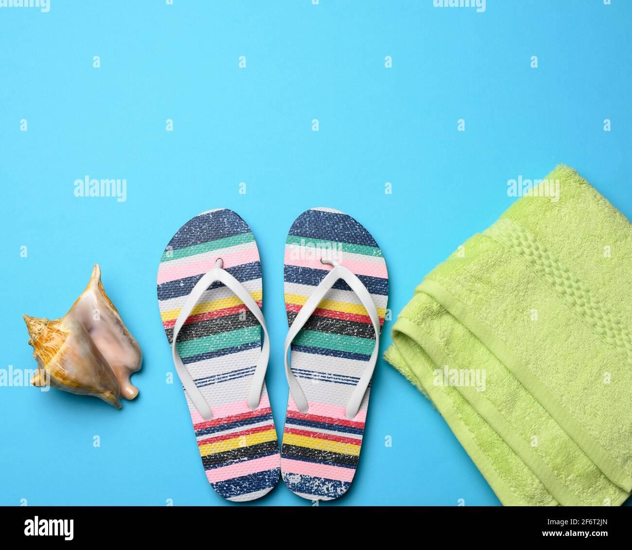 zapatillas de goma a rayas para mujer sobre fondo azul, vista superior, lugar para una inscripción. Foto de stock