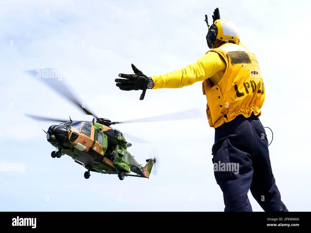 CORAL SEA (Nov 19, 2018) Aviation Boatswainâ.s Mate (Manipulación) Airman Caleb Brawner, de Wichita, Kan. , señala un helicóptero Taipan MRH-90 Foto de stock