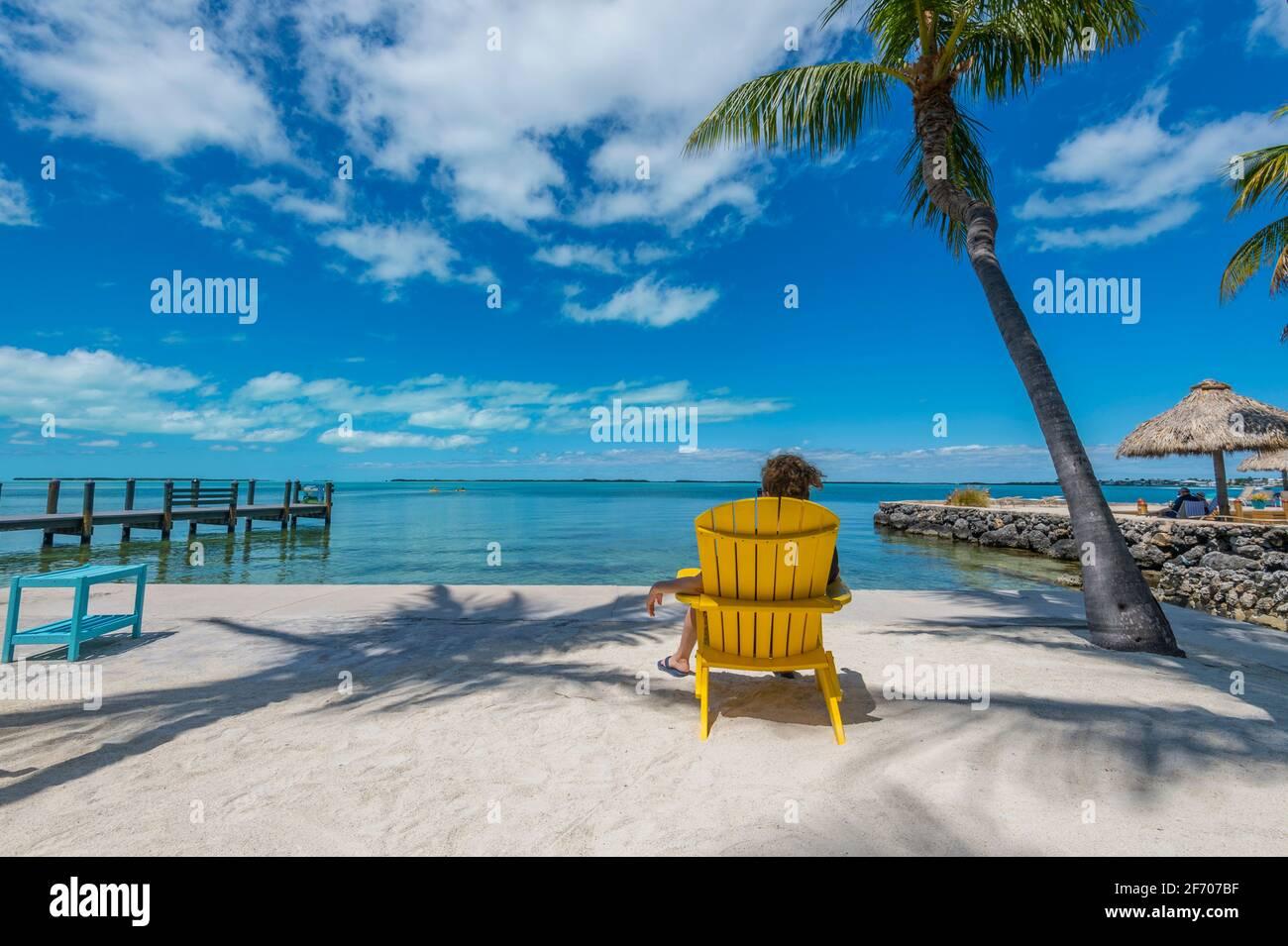 Mujer sentada en silla Adirondack amarilla, mirando contemplativamente al océano Caribe en un día soleado increíblemente hermoso. Foto de stock