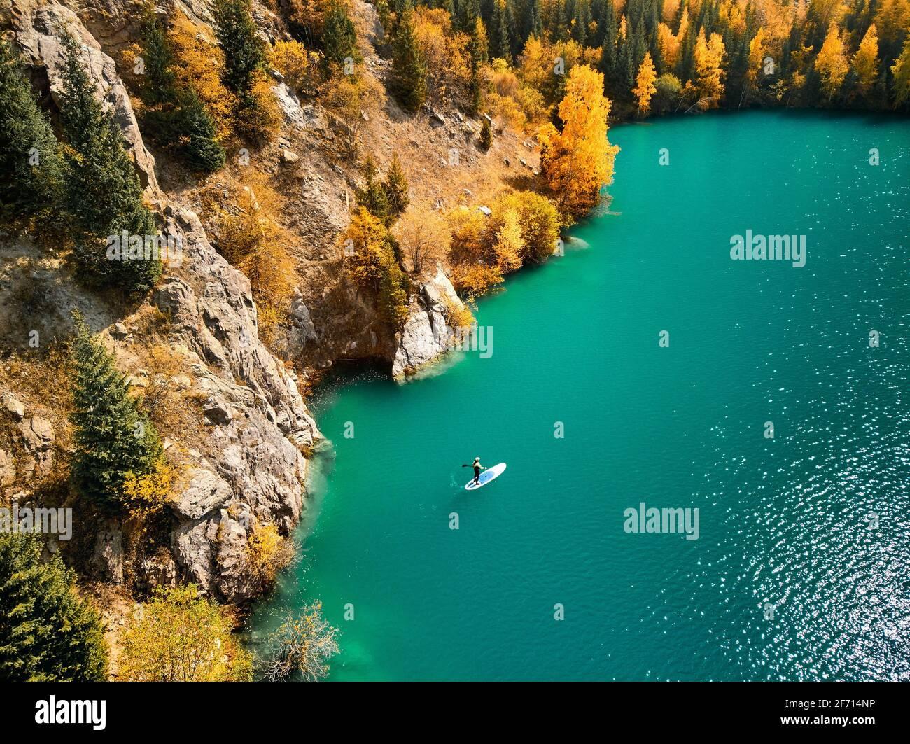 Tiro aéreo de drones de Man flotando en una tabla de SUP en el lago de montaña cerca de bosque amarillo en el otoño. Aventura en Stand up paddle boarding. Foto de stock