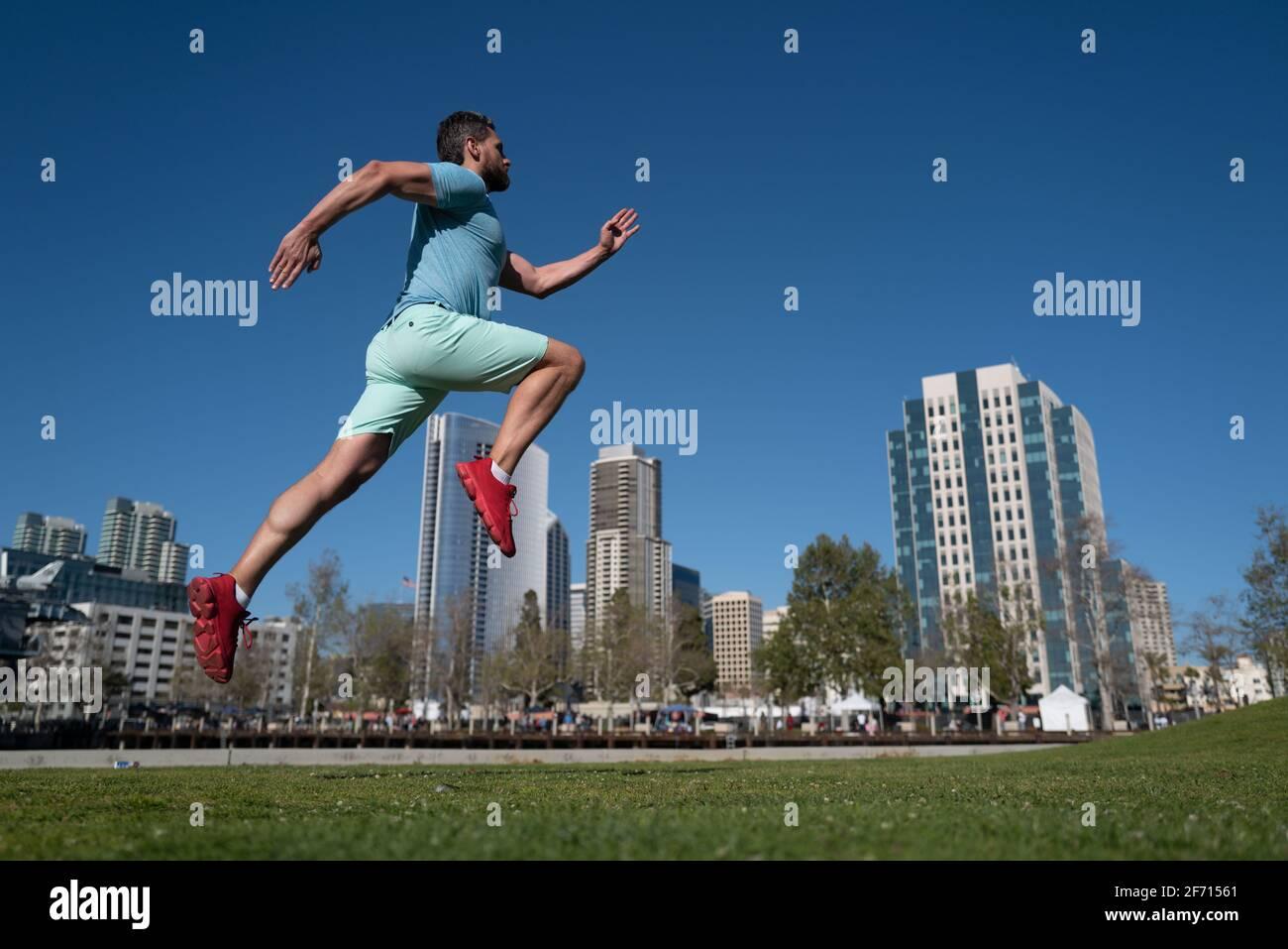 Pies de atleta corriendo en el parque de la ciudad. Concepto de jogging al aire libre. Hombre corriendo para hacer ejercicio sobre el fondo de la ciudad. Foto de stock