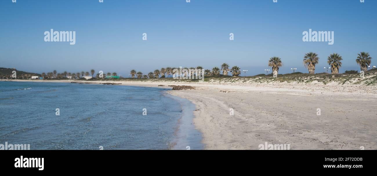Paisaje de una playa italiana en Cerdeña. Cielo azul, arena blanca y agua clara sin gente. Vista natural de la costa del mar durante el encierro del verano Foto de stock