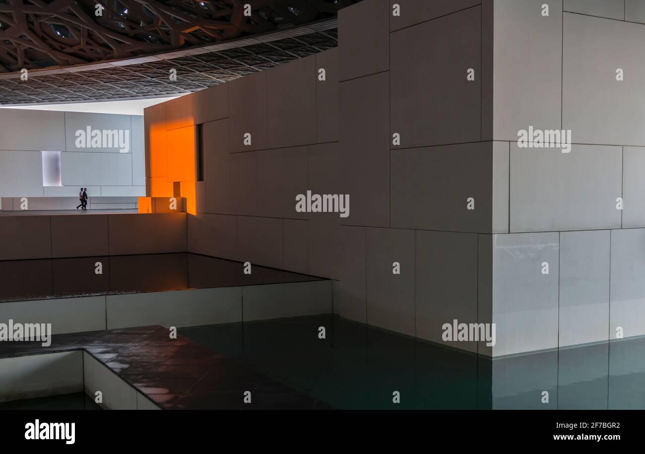 Dos hombres caminando en la dirección de una pared blanca cambiaron a naranja debido a la puesta de sol. Museo del Louvre. Abu Dhabi, Emiratos Árabes Unidos. Foto de stock