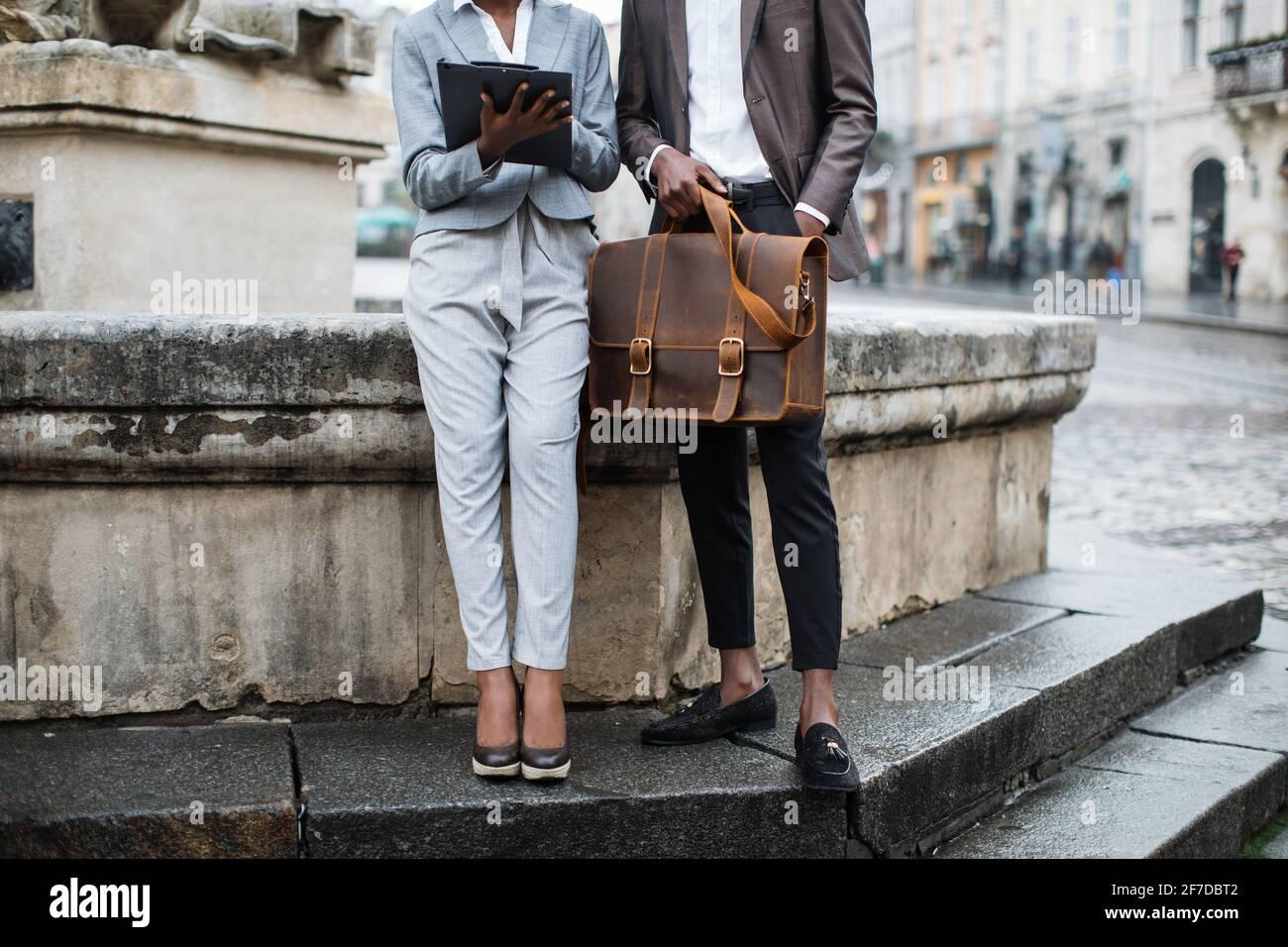 Primer plano de una mujer afro americana con portapapeles y un joven con maletín sentado al aire libre. Dos colegas de negocios resolviendo problemas de trabajo urgentes en la calle. Foto de stock