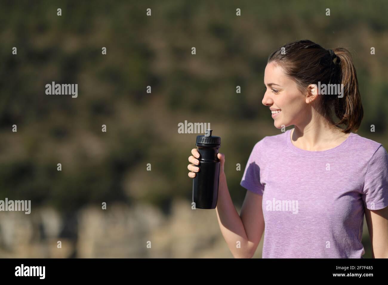 Feliz y hermoso jogger que sostiene una botella de agua contemplando las vistas en el montaña Foto de stock