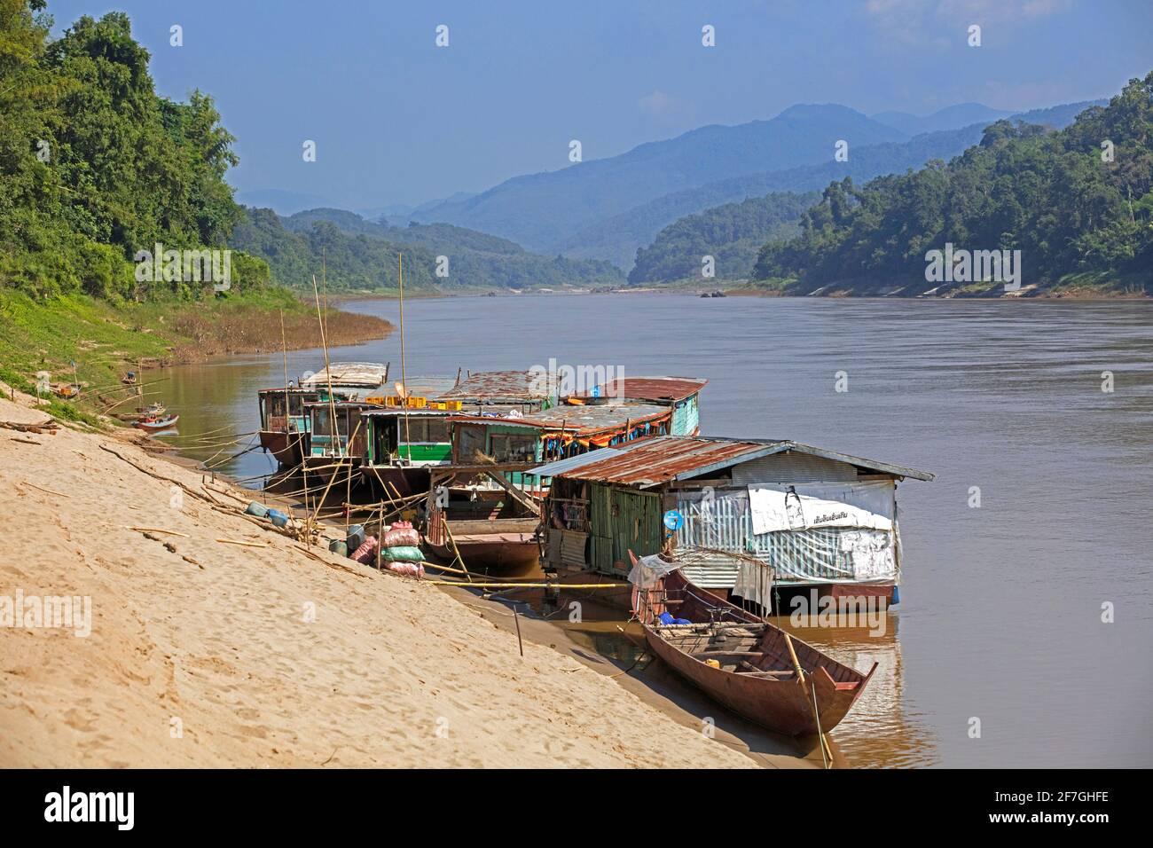 Slowboats / botes lentos para cruceros por el río a Luang Phabang / Luang Prabang / Louangphabang en el río Mekong al atardecer, Laos Foto de stock