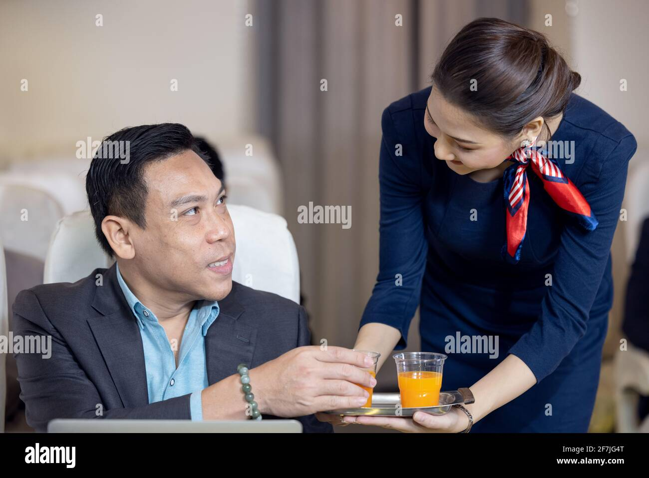 Los pasajeros tienen jugo de naranja servido por una azafata aérea en avión, los asistentes de vuelo sirven a bordo Foto de stock