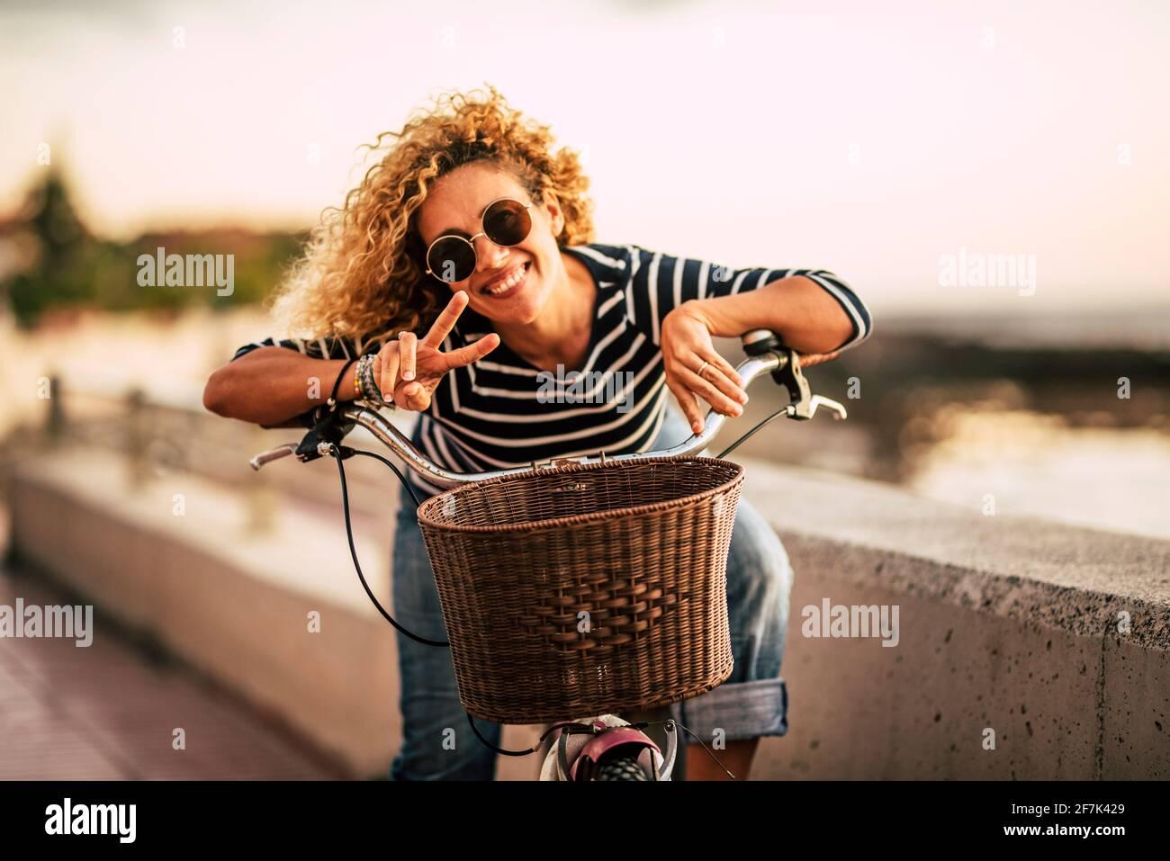 Retrato de una hermosa mujer adulta de mediana edad sonriendo y teniendo diversión mirando la cámara - mujeres activas con la bicicleta y el estilo de vida saludable outdo Foto de stock