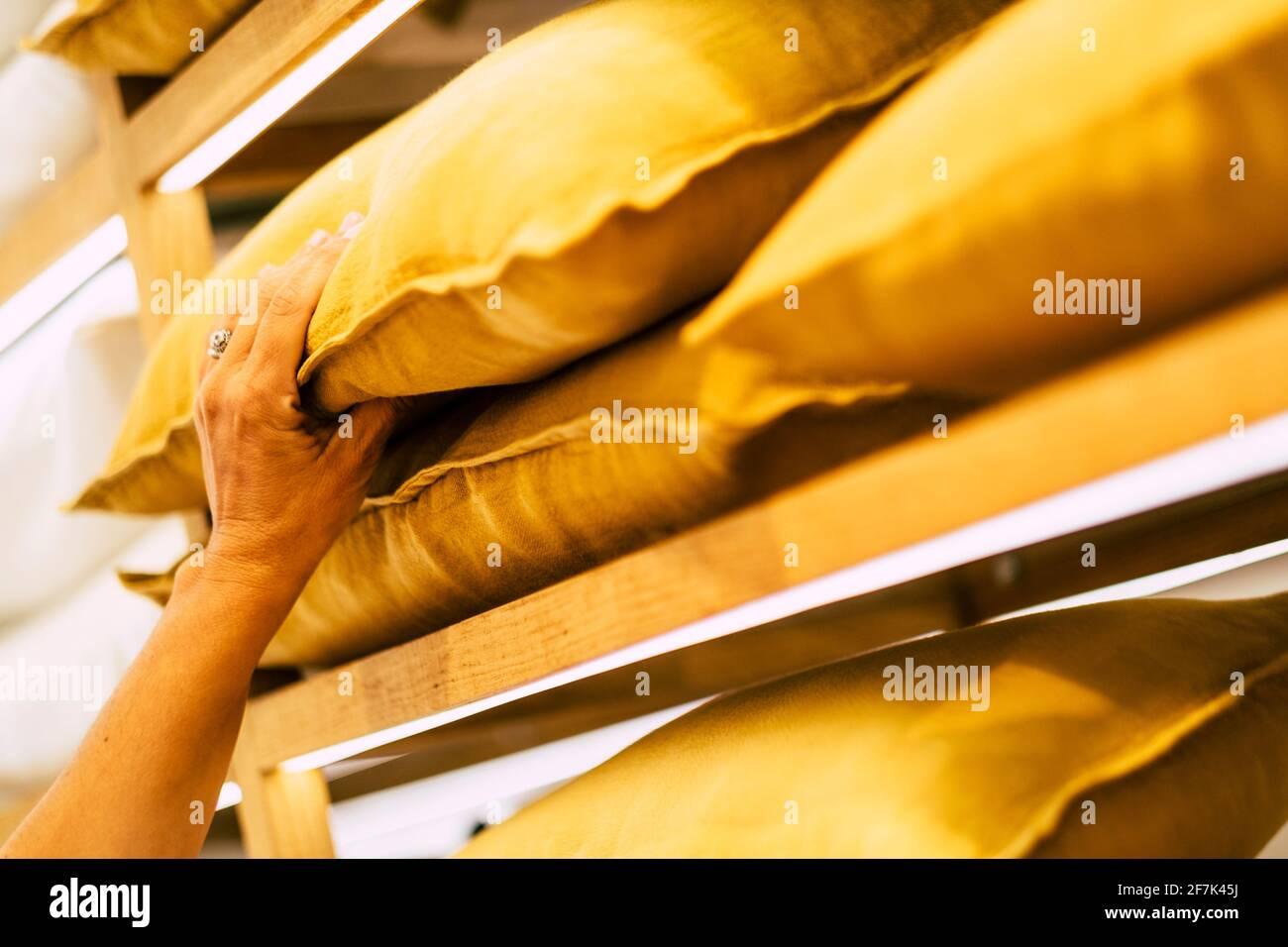 Primer plano de las manos de la mujer tomando y eligiendo la almohada amarilla en la exposición de la tienda Foto de stock