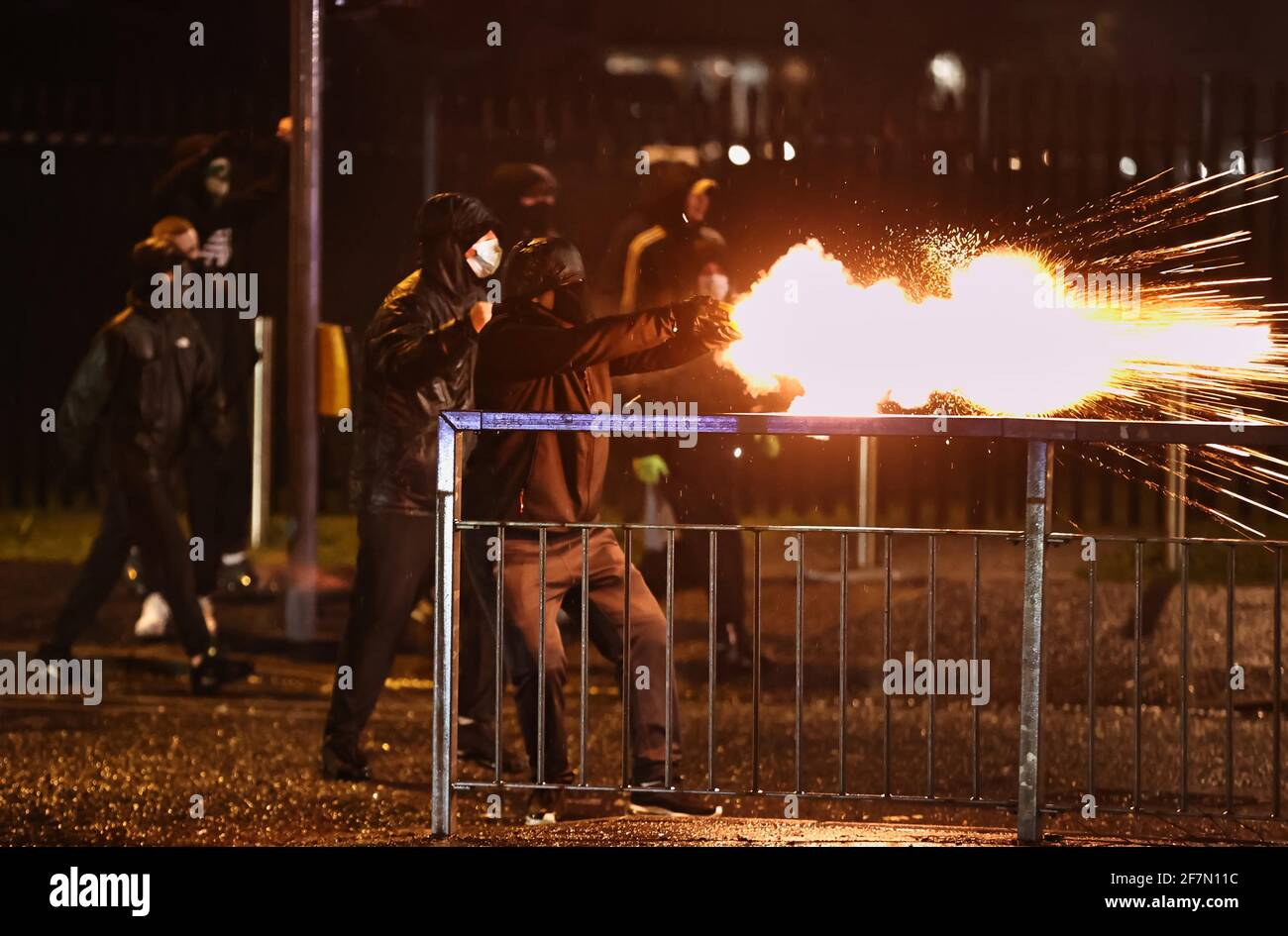 Jóvenes disparan fuegos artificiales en el PSNI en la carretera de Springfield, durante más disturbios en Belfast. Fecha de la foto: Jueves 8 de abril de 2021. Foto de stock