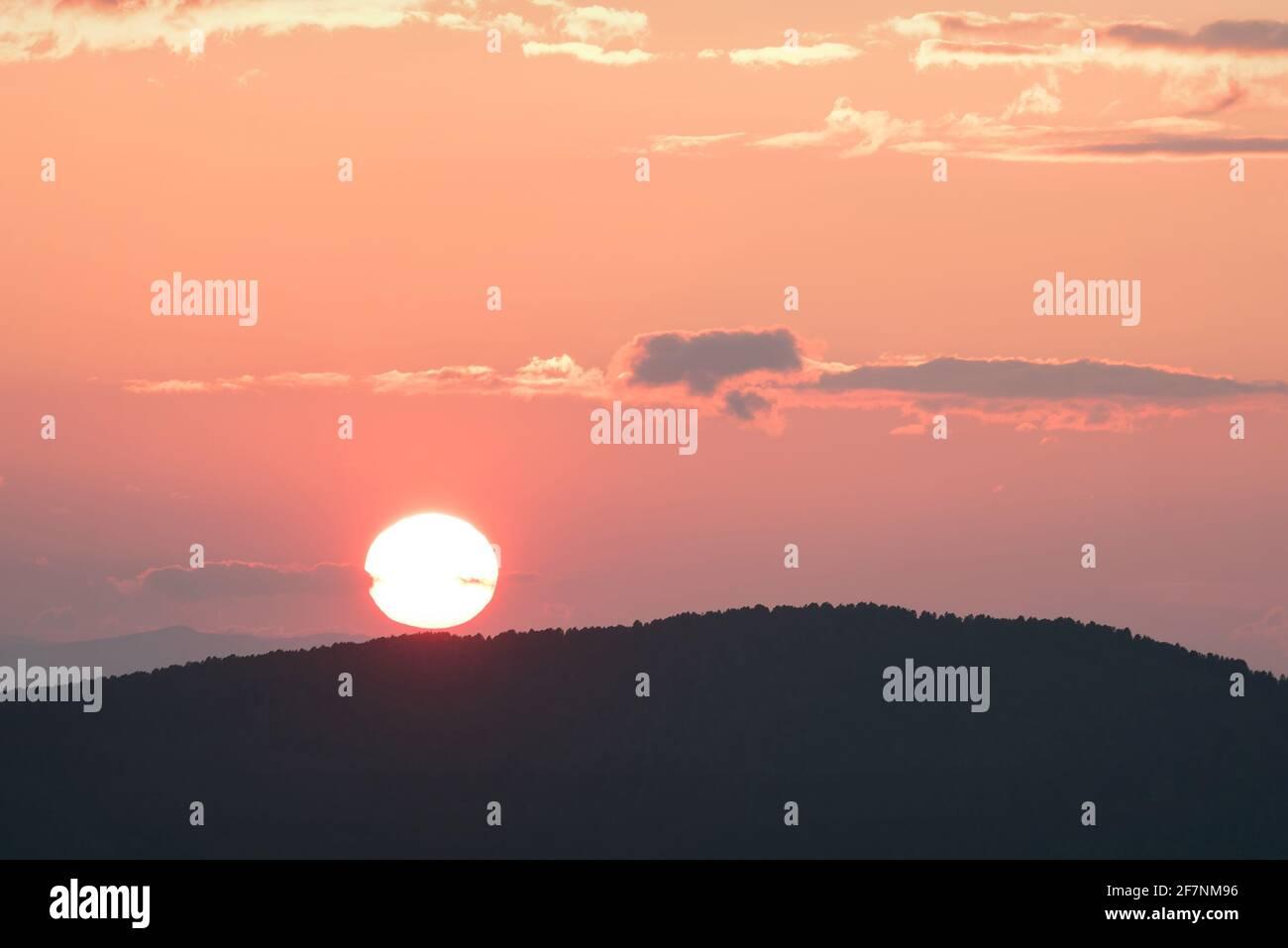 Increíble y delicada puesta de sol rosa con un disco redondo para el sol los contornos de las montañas cubiertas de bosque y nubes iluminadas en el cielo Foto de stock