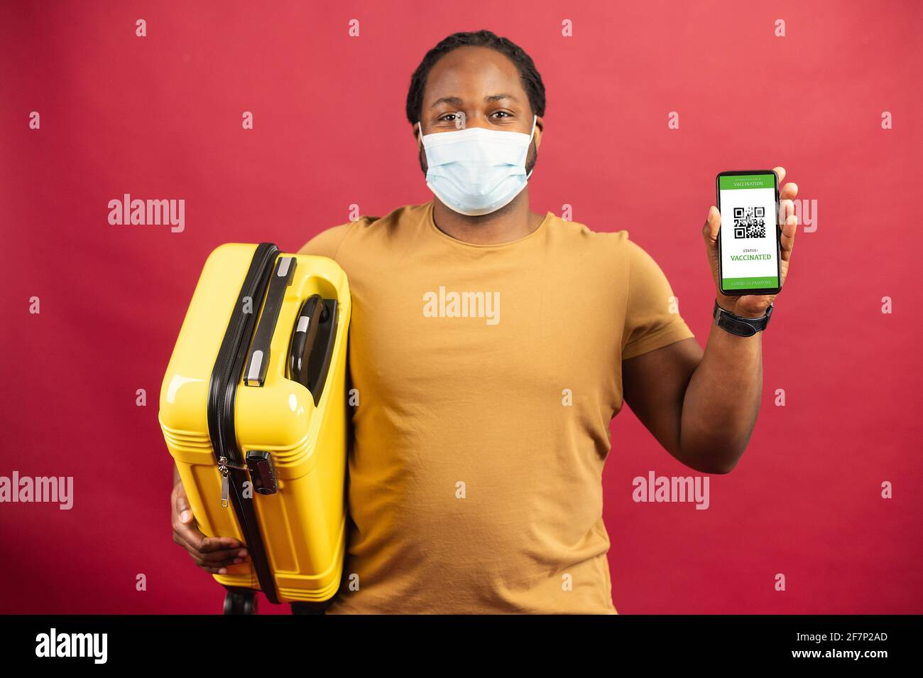 Feliz hombre africano en máscara médica de pie sobre el fondo rojo sosteniendo un bolso amarillo para viajar y celular con código QR en la pantalla, concepto de visualización de boletos sin contacto, paso seguro de aduanas Foto de stock