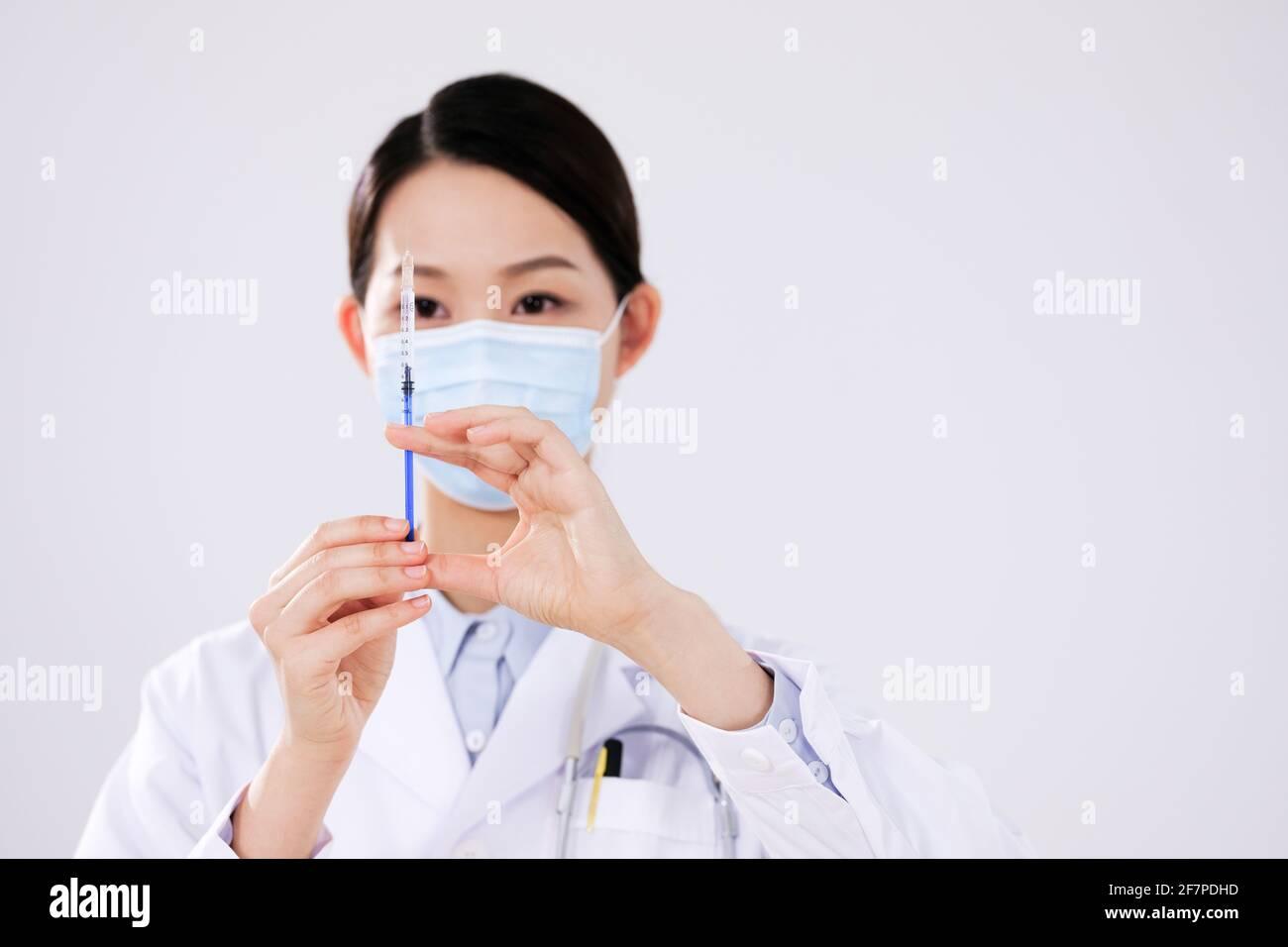 Una mujer médica con una máscara usa una jeringa en la parte delantera ver Foto de stock