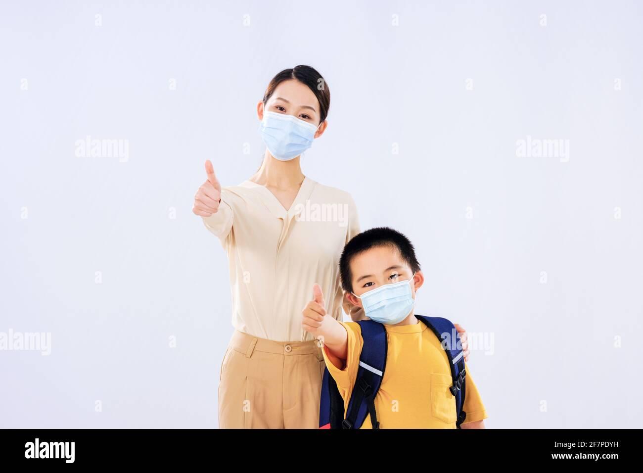 Mamá y el niño pequeño con la máscara puesta sus pulgares sonriendo Foto de stock