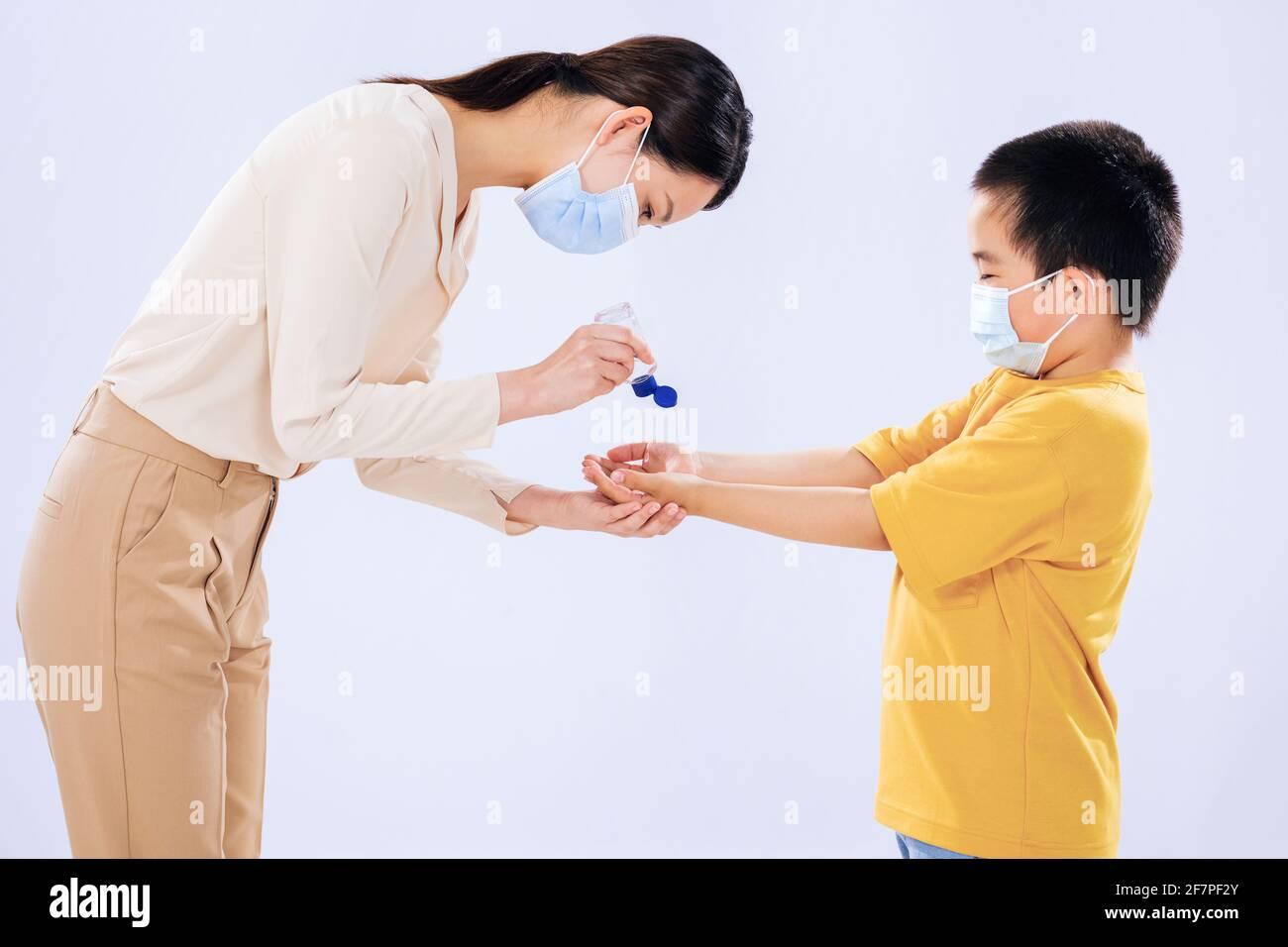 La madre le enseñó al niño a usar desinfectante para manos con su mamá Foto de stock