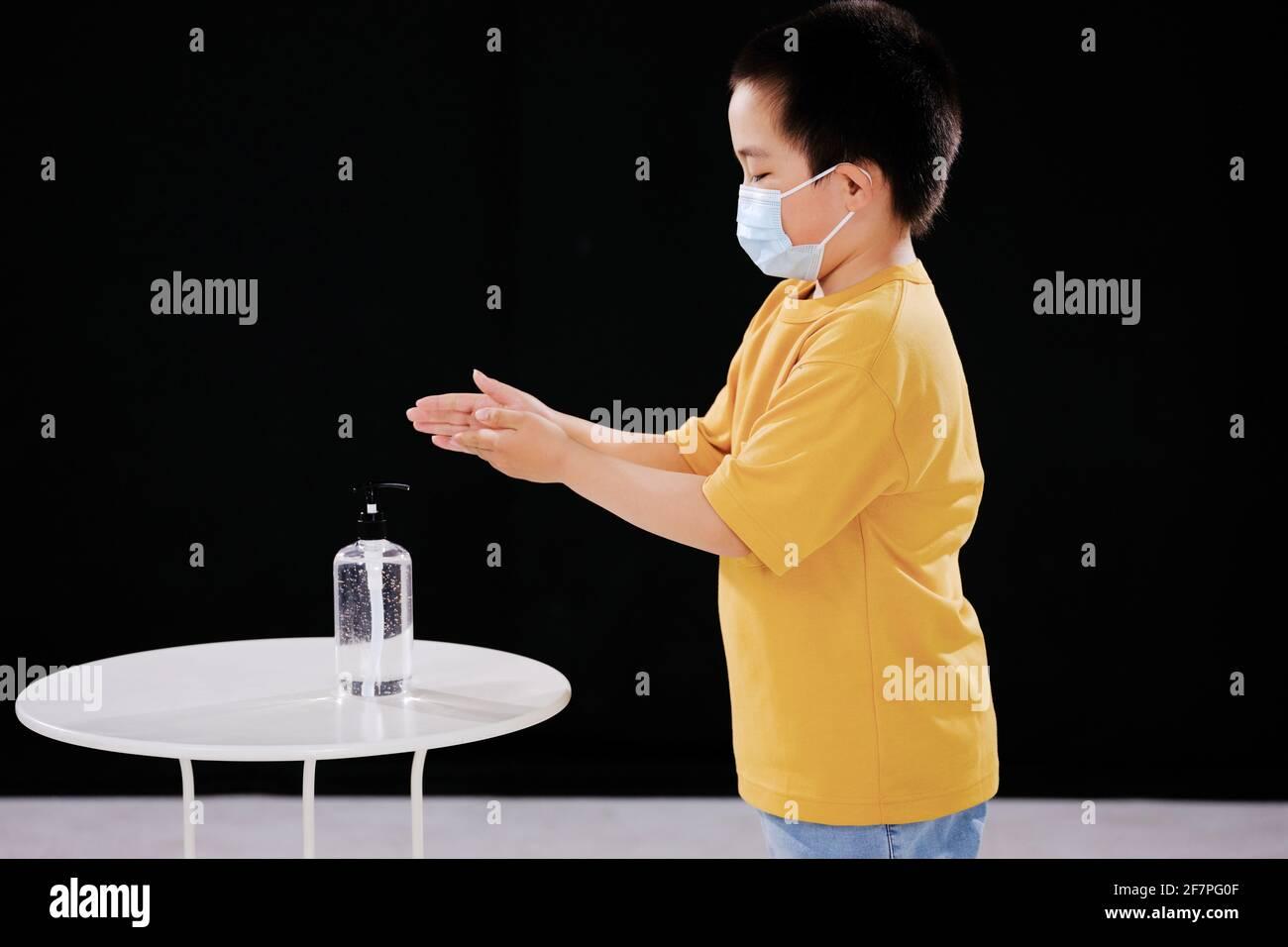 Un niño pequeño con máscaras usa desinfectante para manos Foto de stock