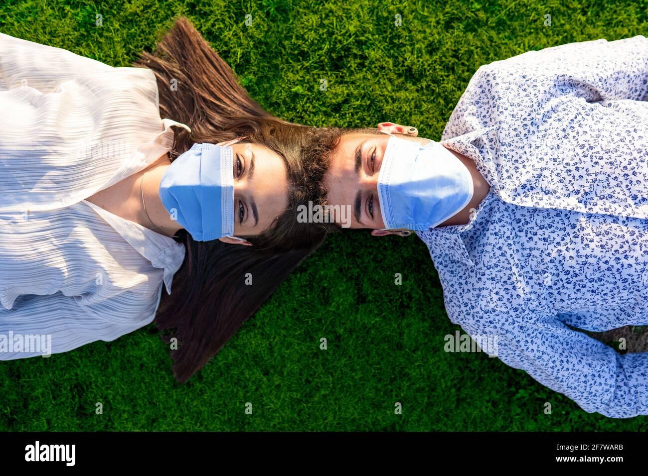 Hermosa pareja de jóvenes estudiantes acostados de cabeza a cabeza está detrás del césped verde del parque de la ciudad con vistas al cámara con la máscara protectora contra Foto de stock