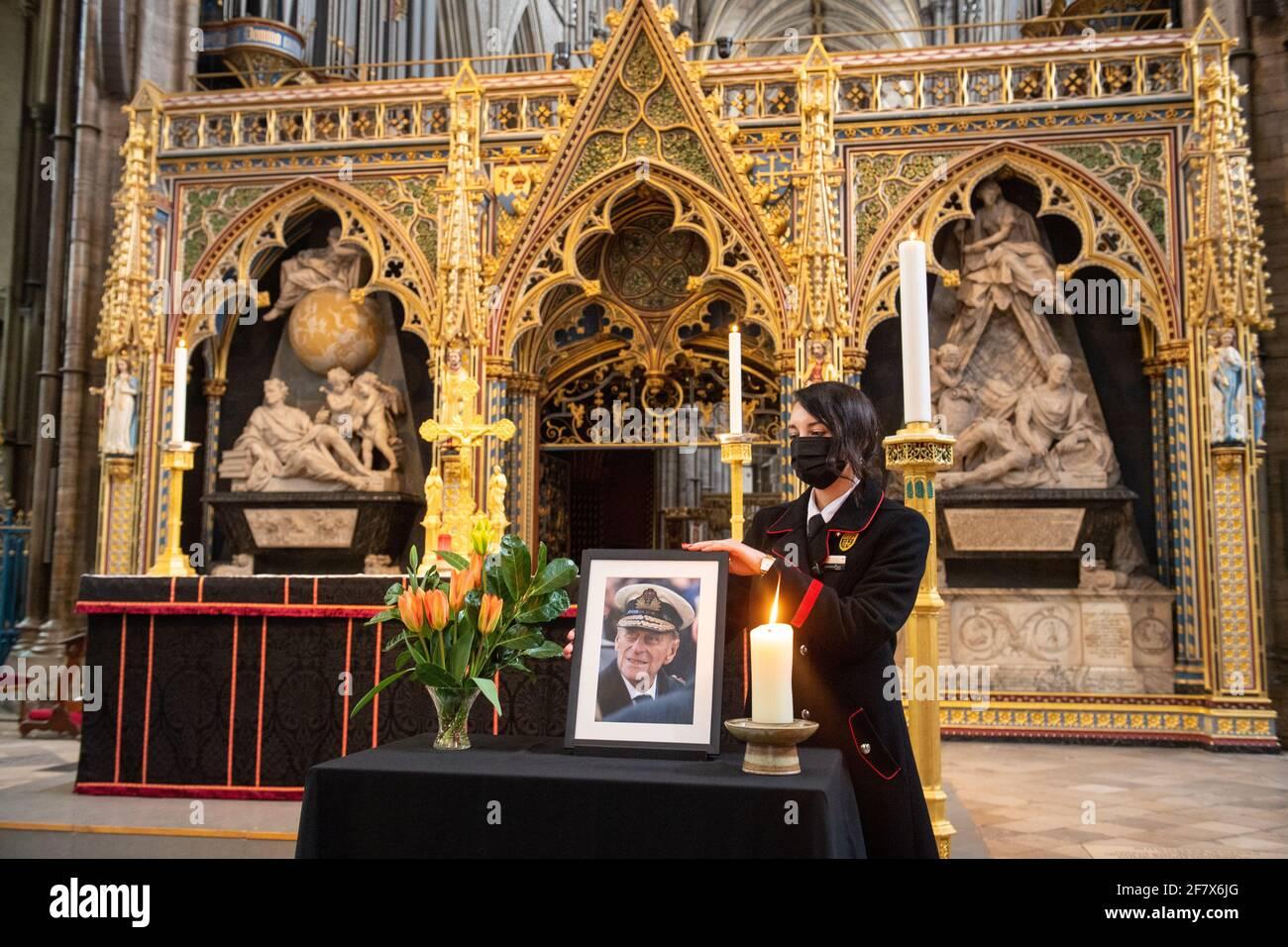 Rosa Wlodarczyk ajusta una fotografía del duque de Edimburgo que se exhibe junto a la nave en la Abadía de Westminster, Londres, que ha sido vestida de negro para marcar su muerte. Fecha de la foto: Sábado 10 de abril de 2021. Foto de stock