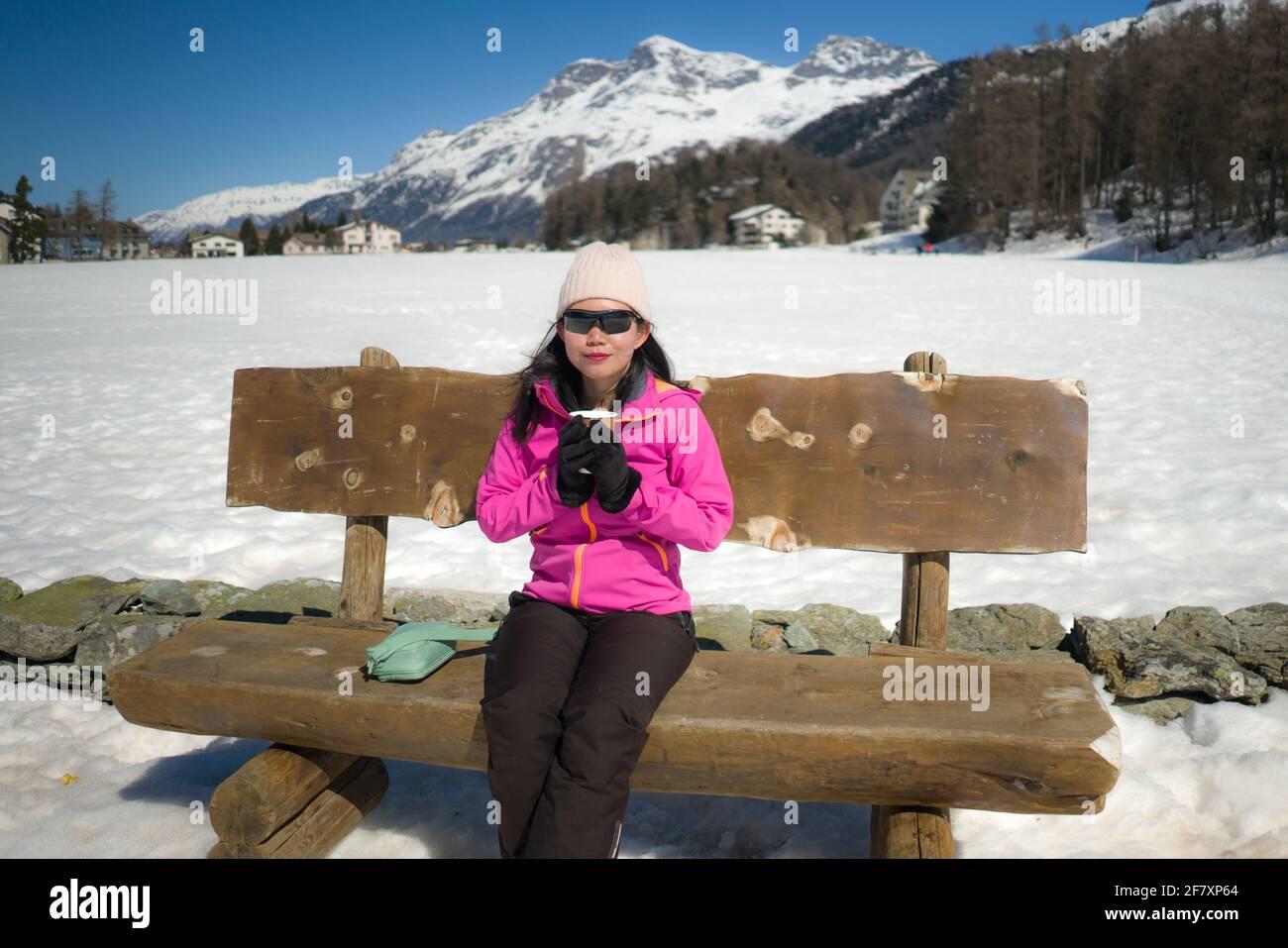 Congelación Vacaciones de invierno - jóvenes felices y hermoso asiático coreano mujer en el banco en el paisaje helado del lago rodeado de nieve Montañas disfrutando de Suiza Foto de stock