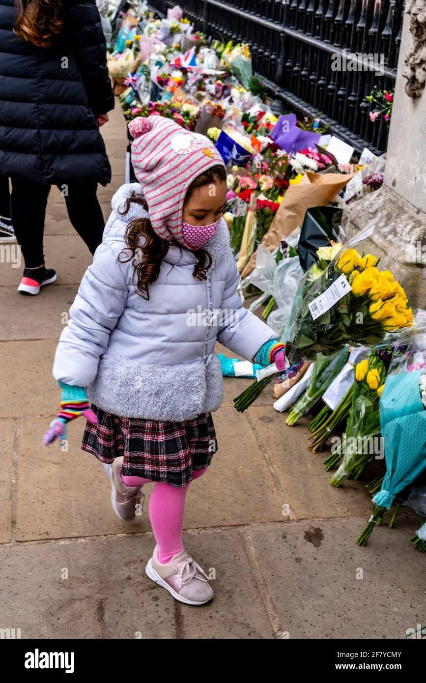 Buckingham Palace, Londres, Reino Unido. 10th de Abr de 2021. Un niño pone flores fuera del Palacio de Buckingham en memoria del Duque de Edimburgo (Príncipe Felipe) que falleció el 9th de abril. Crédito: Grant Rooney/Alamy Live News Foto de stock