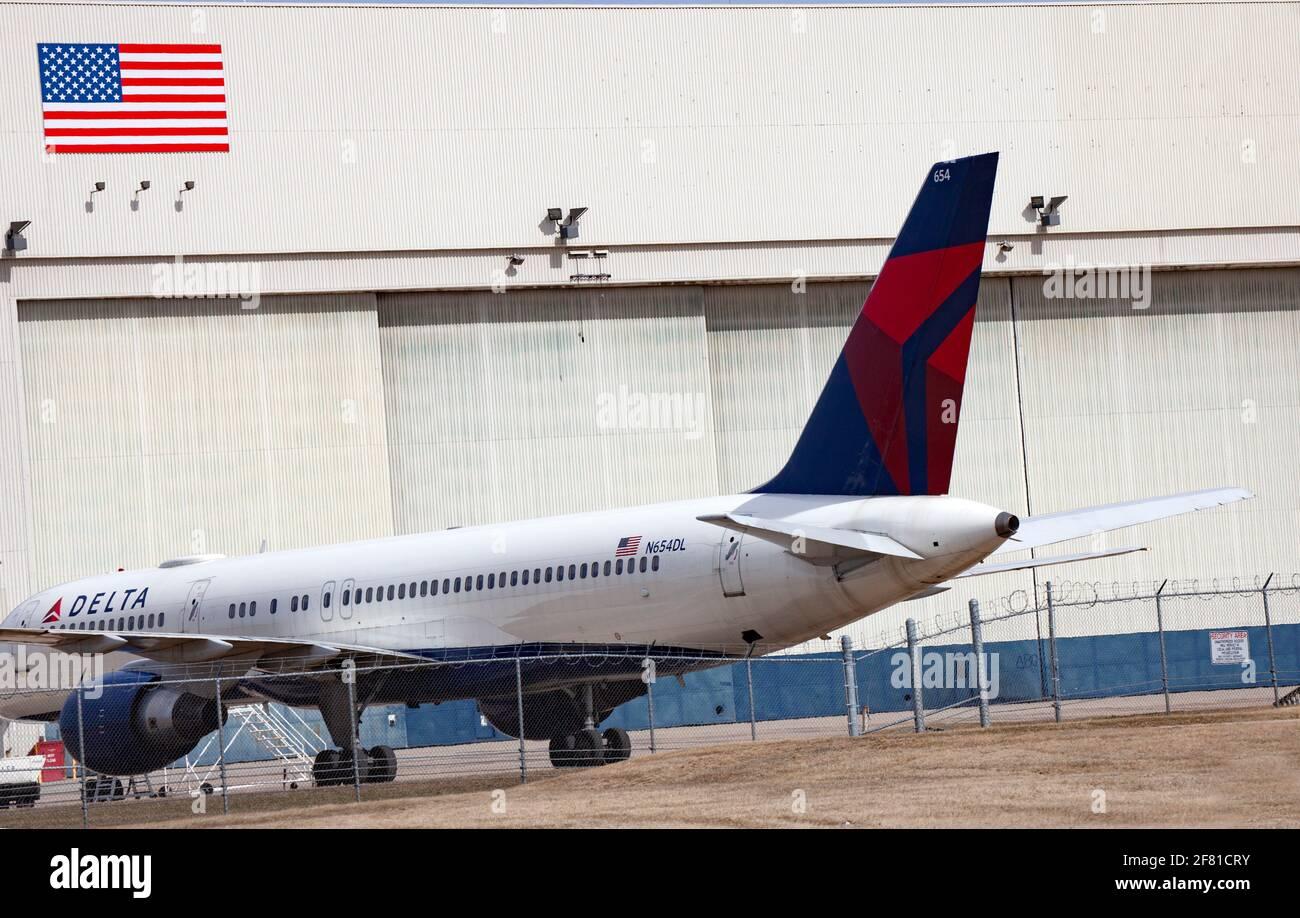 Delta Airplane estacionado con hangar y bandera americana en el fondo en el Aeropuerto Internacional St Paul de Minneapolis. Minneapolis Minnesota MN Estados Unidos Foto de stock