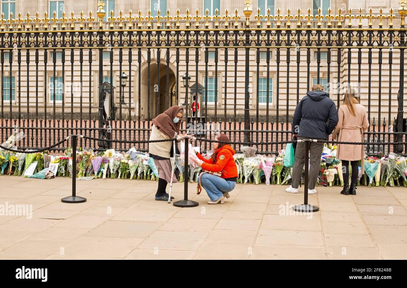Buckingham Palace en Londres, Miembros del público que ponen flores por la muerte del príncipe Felipe, el duque de Edimburgo. Londres, Reino Unido, 10th de abril de 2021 Foto de stock