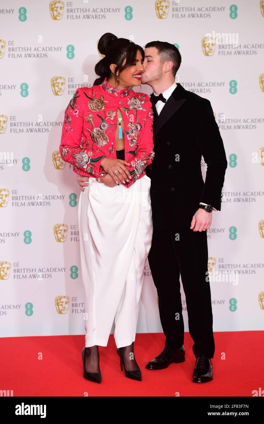 Priyanka Chopra Jonas y su marido Nick Jonas llegan a los EE BAFTA Film Awards en el Royal Albert Hall de Londres. Fecha de la foto: Domingo 11 de abril de 2021. Foto de stock