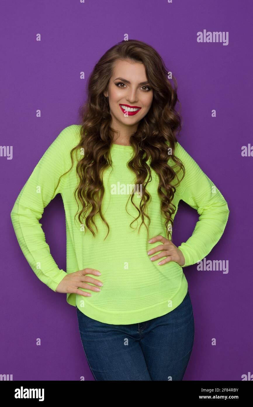 Mujer joven casual en verde neón limón suéter está posando con las manos en la cadera. Estudio con cintura para arriba sobre fondo morado. Foto de stock