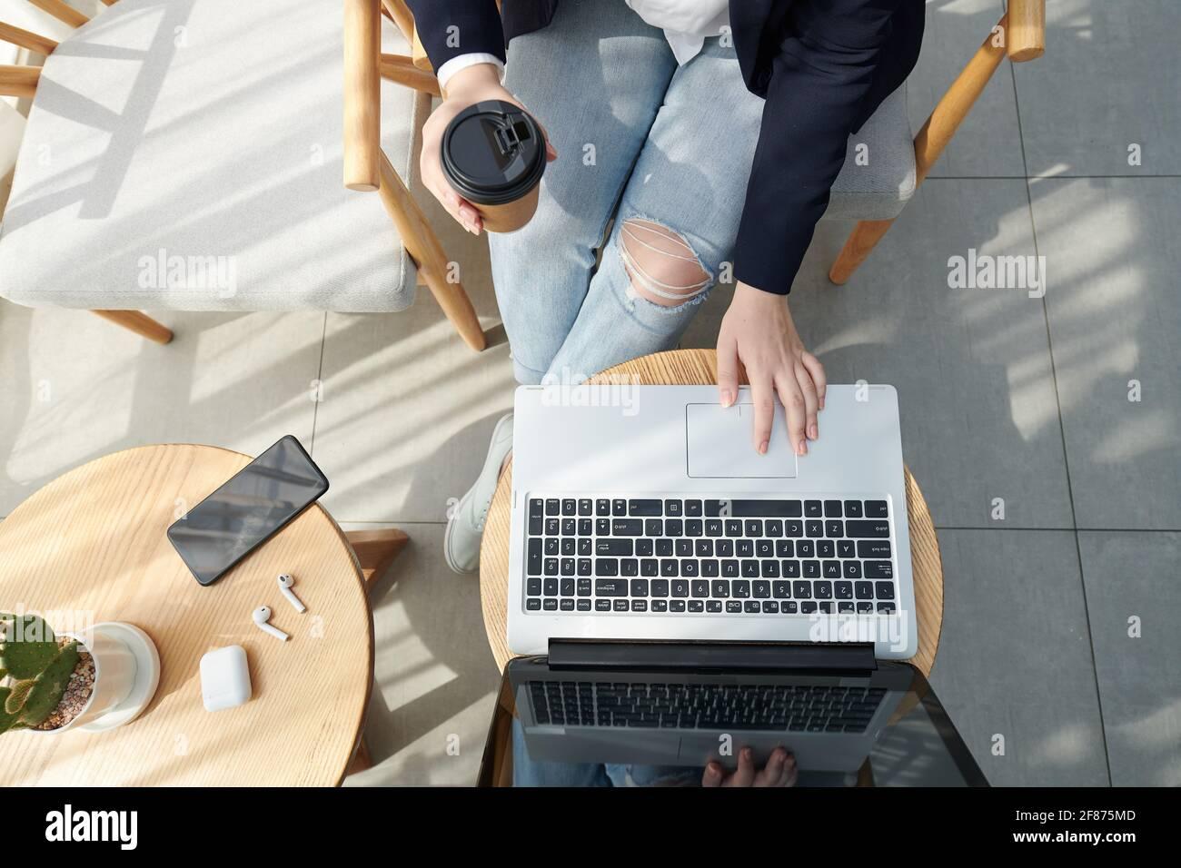 Manos de una estudiante universitaria bebiendo café y trabajando en un ordenador portátil, estudiando y trabajando en un proyecto, vista desde arriba Foto de stock