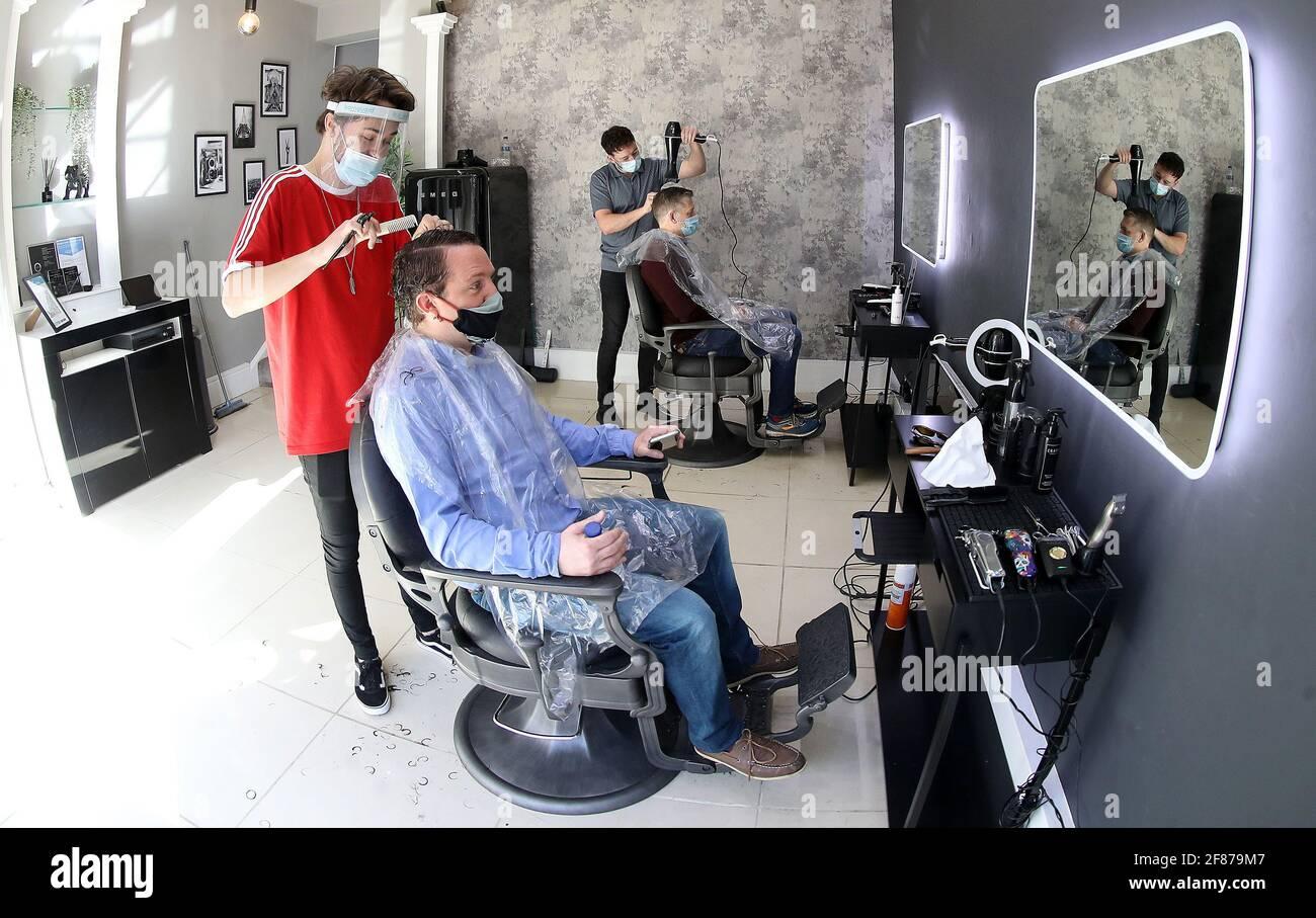 Luke Nancollis (izquierda) corta el pelo de John-Paul Jeffs en la reapertura de la peluquería de caballeros Crate en Knutsford, Cheshire, mientras Inglaterra da otro paso atrás hacia la normalidad con la mayor relajación de las restricciones de cierre. Fecha de la foto: Lunes 12 de abril de 2021. Foto de stock