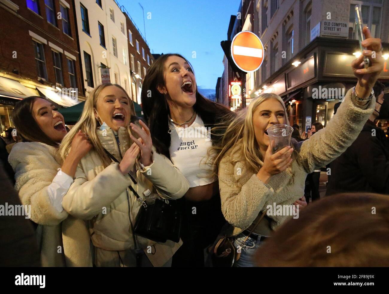 La gente celebra estar fuera por la noche en Old Compton Street, Soho, en el centro de Londres, donde las calles se han cerrado al tráfico para crear zonas de estar al aire libre para los bares y restaurantes de reapertura, ya que Inglaterra da un paso más hacia la normalidad con la mayor relajación de las restricciones de bloqueo. Fecha de la foto: Lunes 12 de abril de 2021. Foto de stock