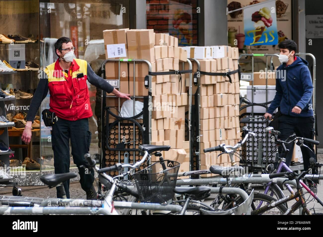 Berlín, Alemania. 12th de Abr de 2021. Un mensajero que lleva una máscara lleva paquetes en Berlín, capital de Alemania, el 12 de abril de 2021. Más de tres millones de infecciones por COVID-19 se han registrado en Alemania el lunes desde el brote de la pandemia, según el Instituto Robert Koch (RKI). Crédito: Stefan Zeitz/Xinhua/Alamy Live News Foto de stock