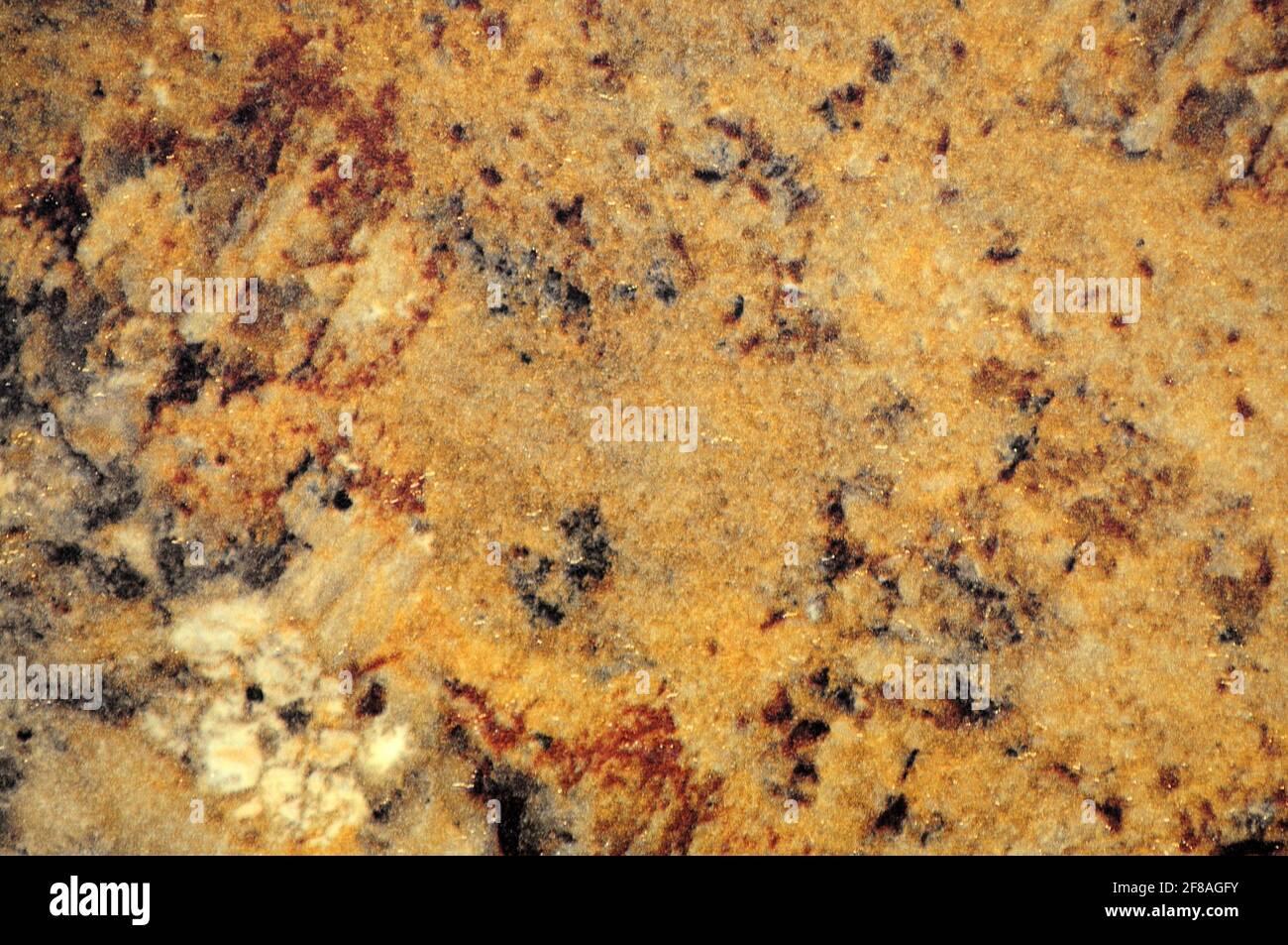 Auricular marrón claro, una superficie plana de piedra natural con manchas oscuras y claras en primer plano. Fondo, patrón, textura. Foto de stock